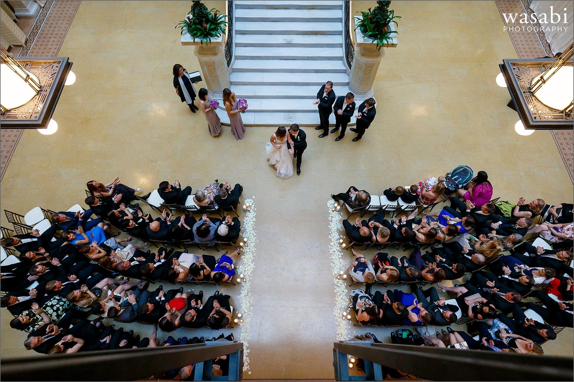wide angle view from the stairs looking straight down after wedding ceremony concludes The Rookery Building in Chicago