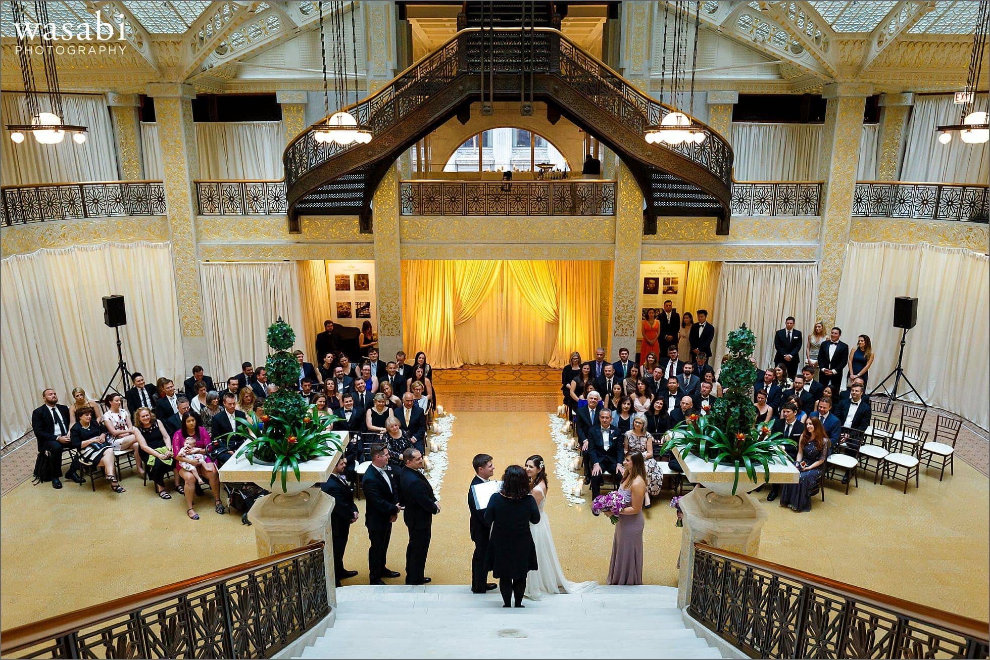 wide angle view of The Rookery wedding photos during ceremony at The Rookery Building in Chicago with stairs in forground and background