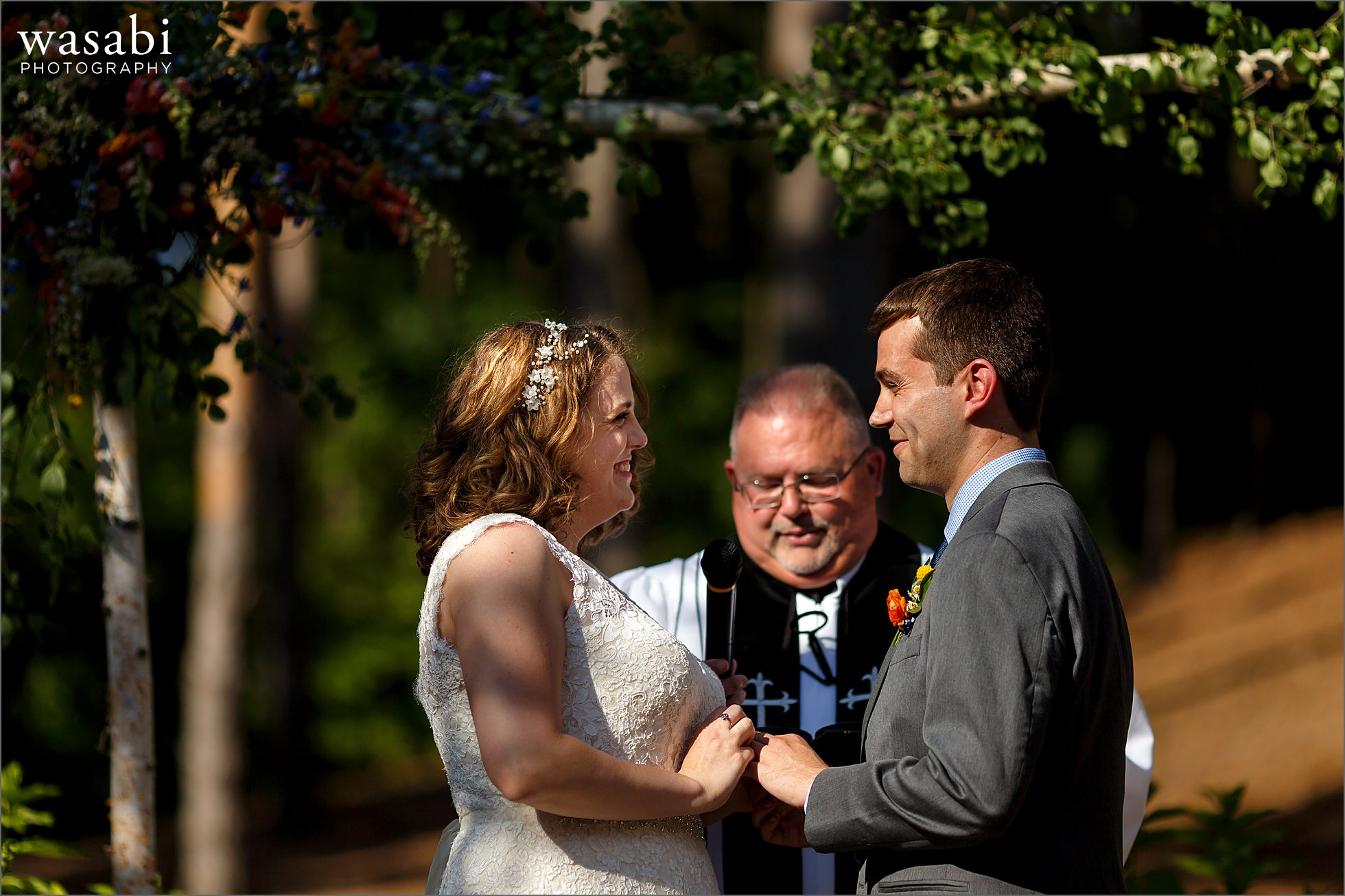 bride and groom exchange rings Oakhurst Country Club wedding photos during outdoor ceremony in Clarkston, Michigan