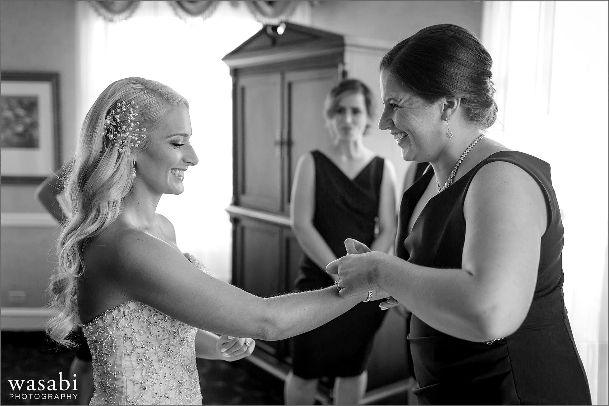 bride and sister smile while putting on bracelet while getting ready for her wedding at Drake Hotel in Chicago