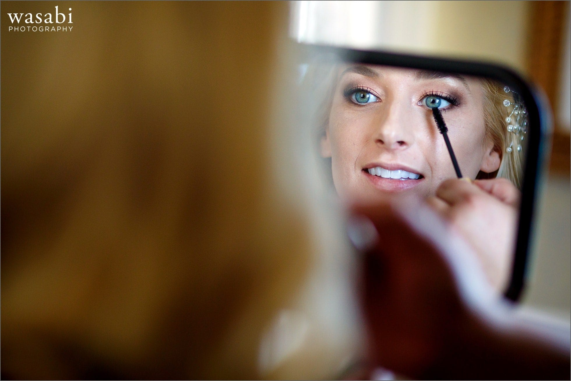 bride has mascara applied to her eyelashes in hand mirror while having her makeup done for her wedding at Drake Hotel in Chicago