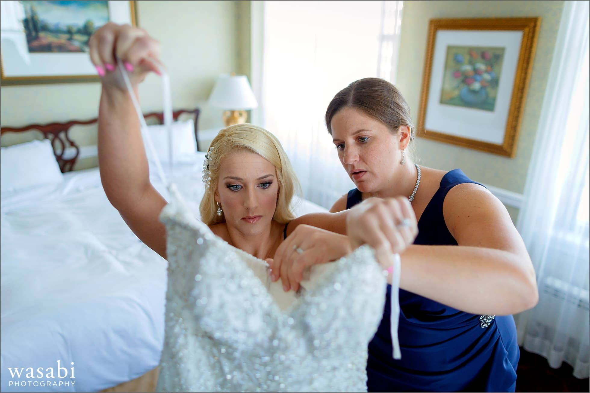 bride steps into her wedding dress with help from her sister while getting ready at Drake Hotel in Chicago