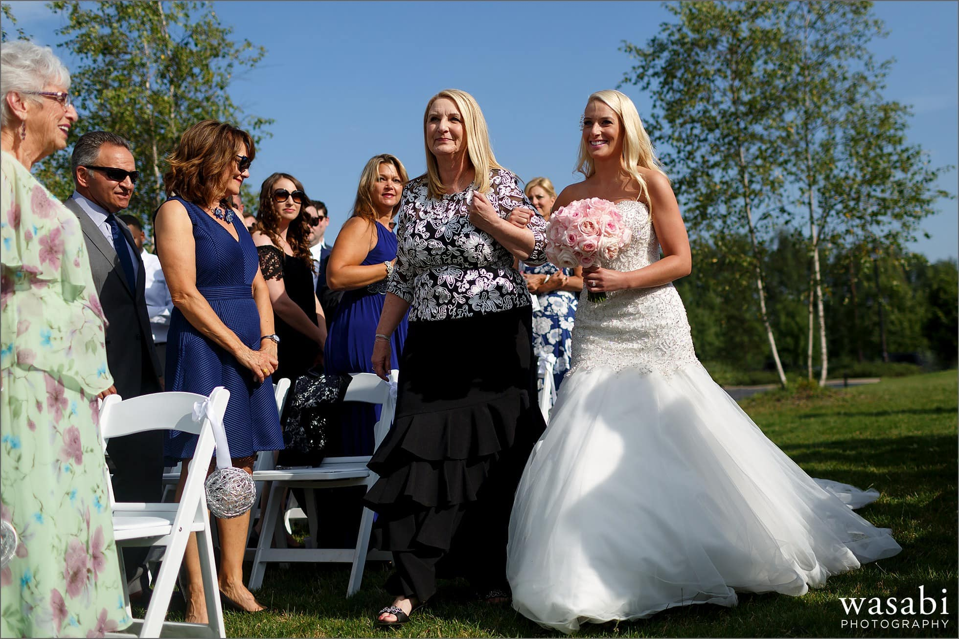 bride walks down aisle with mother during outdoor wedding at at Crystal Tree Country Club in Orland Park