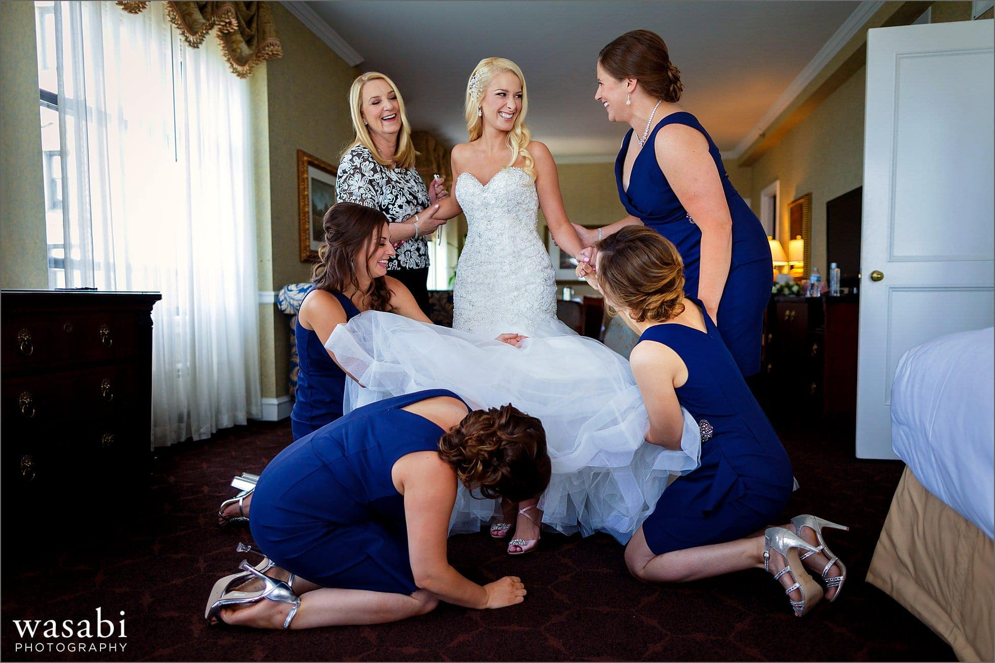 bridesmaids laugh while helping bride put on her shoes while getting ready for her wedding at Drake Hotel in Chicago