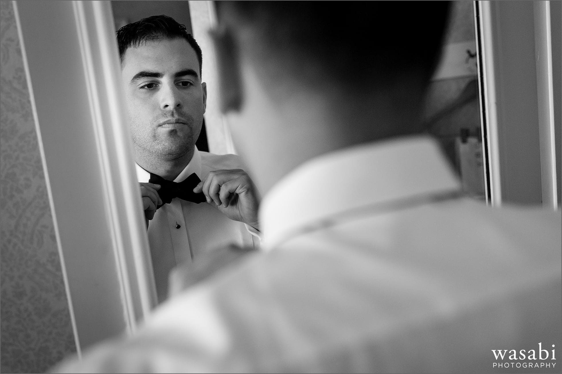 groom adjusts bow tie while getting ready for wedding at Drake Hotel in Chicago