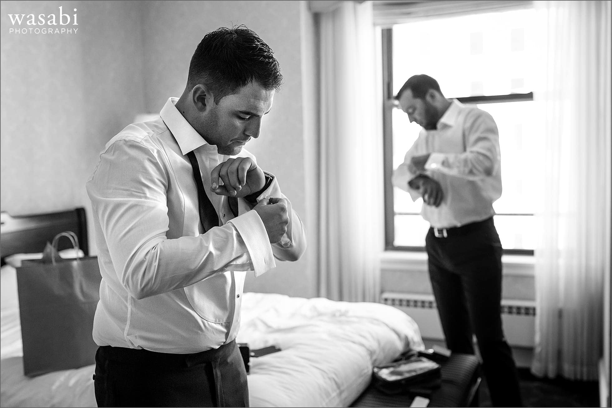 groom and groomsman adjust cufflinks while getting ready for wedding at Drake Hotel in Chicago