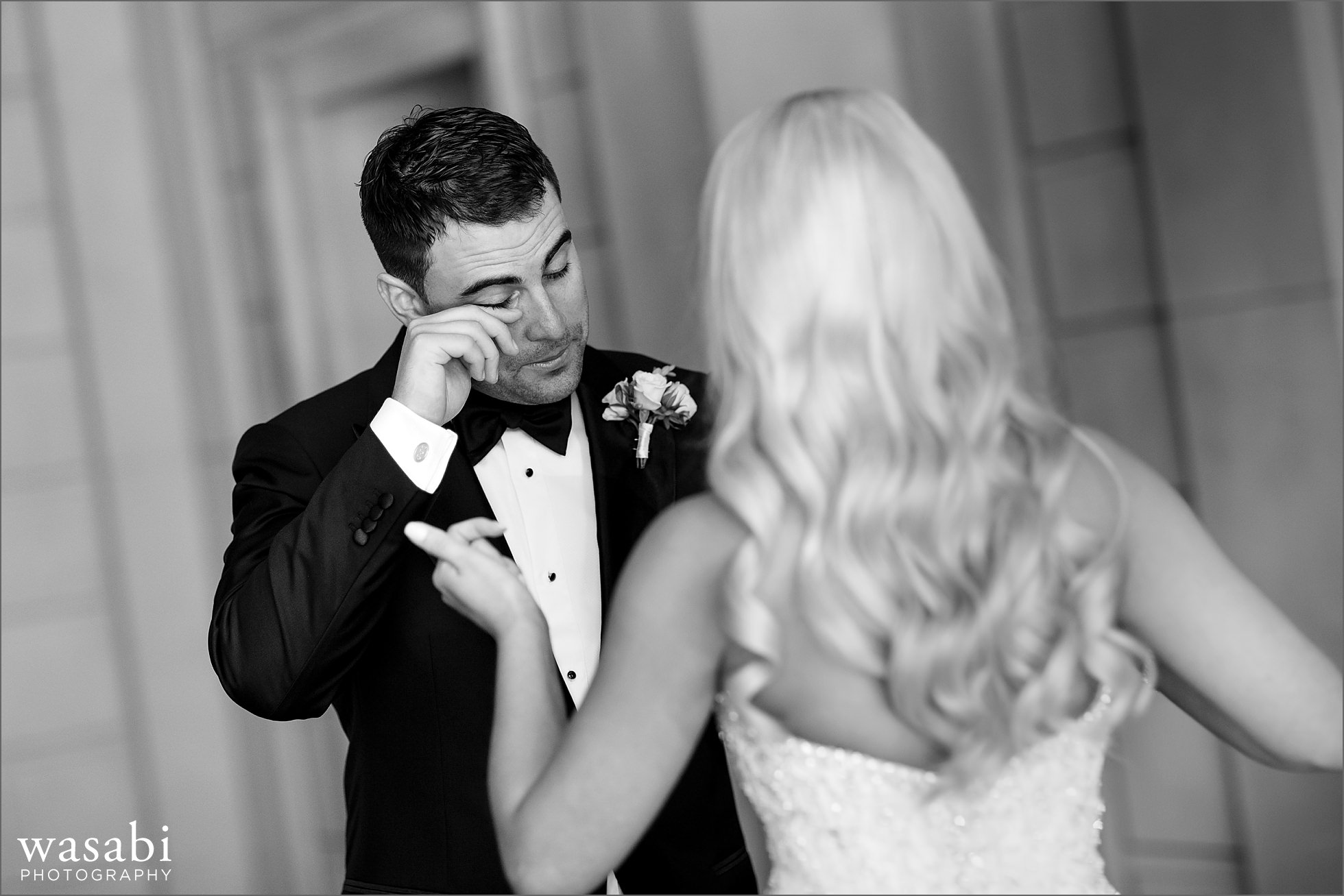 groom wipes away tear after seeing his bride during a first look before their wedding at Drake Hotel in Chicago