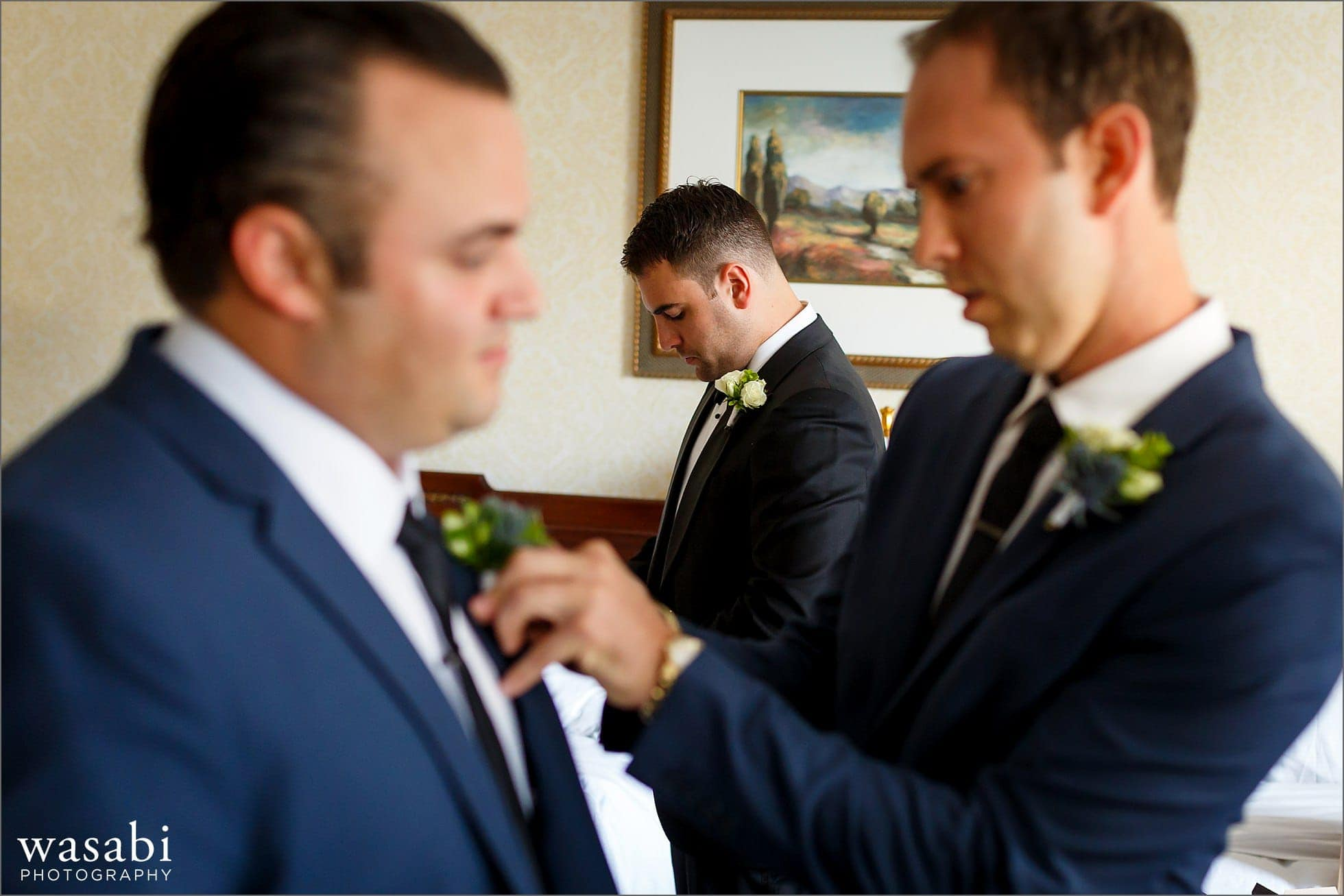 groomsmen put on boutonnieres while getting ready for wedding at Drake Hotel in Chicago