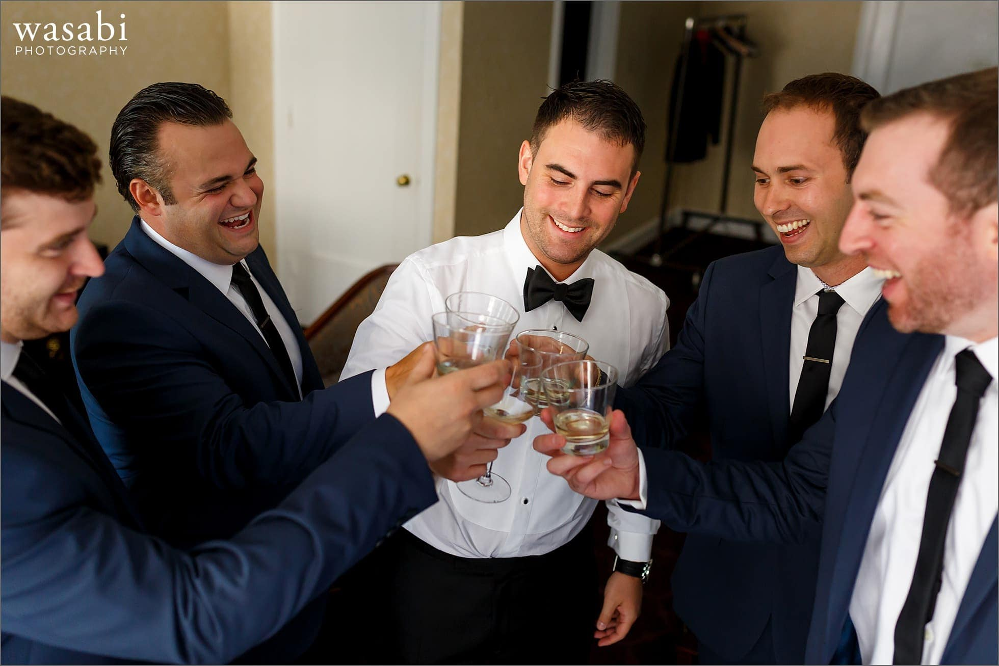 groomsmen toast the groom while getting ready for Drake Hotel wedding in Chicago