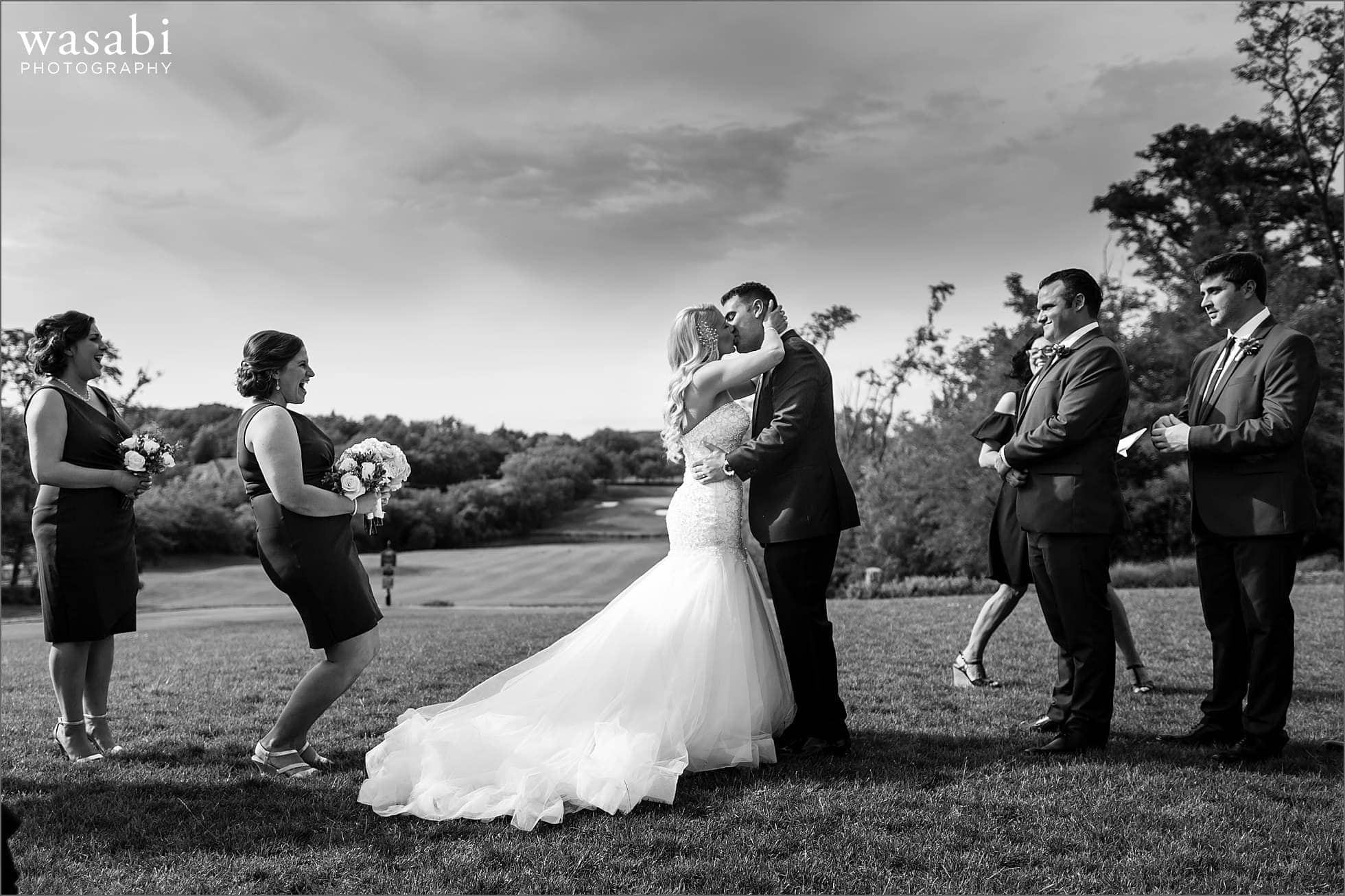 wide angle outdoor golf course ceremony bride and groom first kiss during Crystal Tree Country Club in Orland Park wedding photos