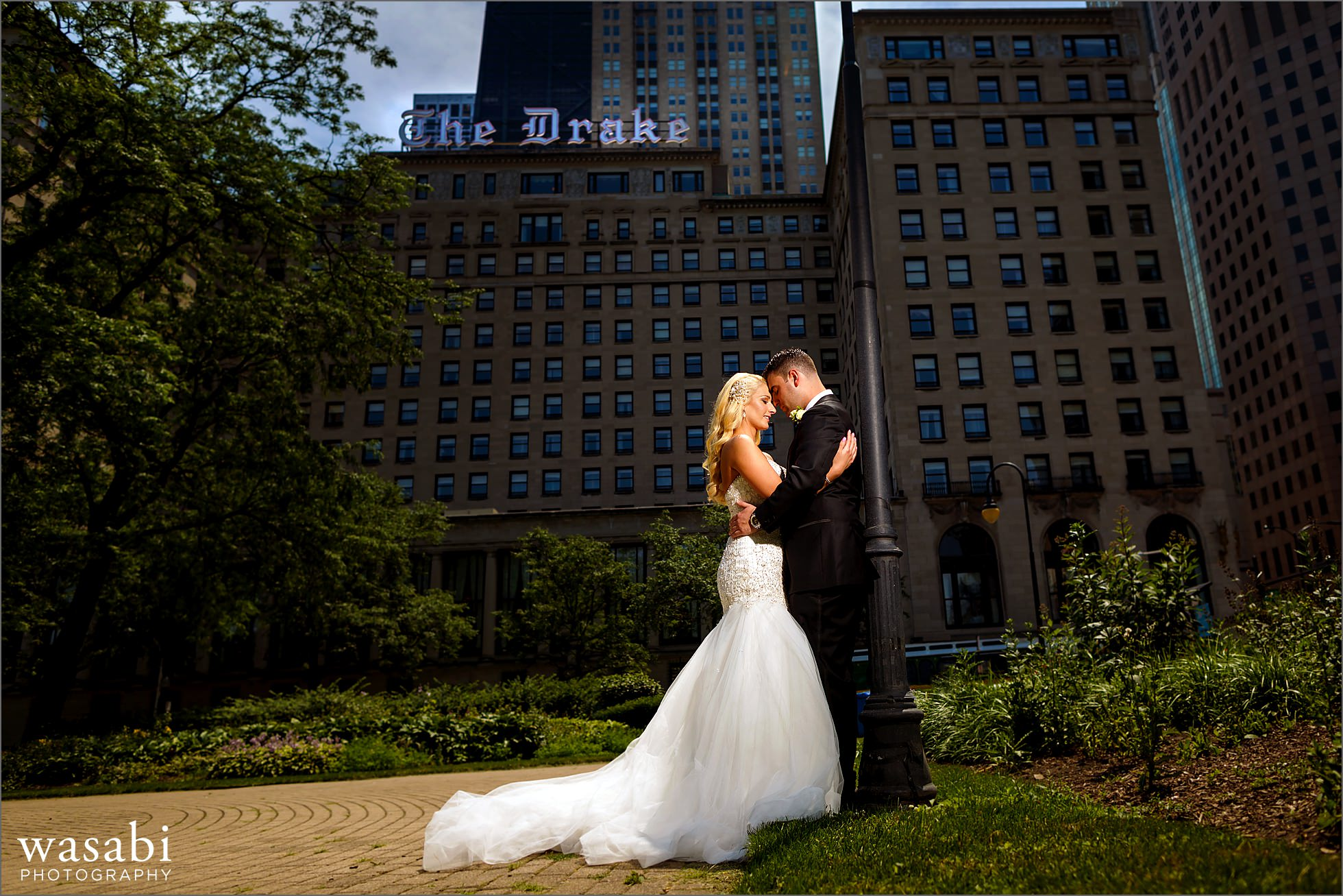 wide angle wedding photo of bride and groom couple with The Drake Hotel in the background