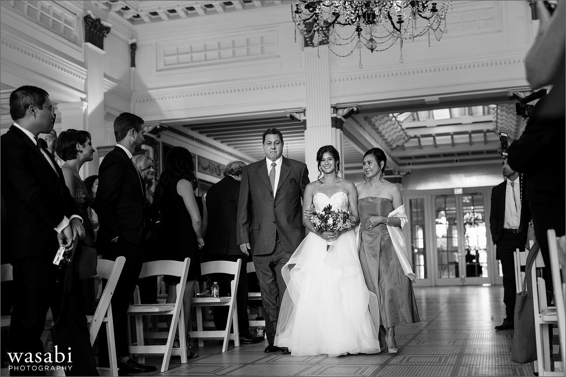 black and white bride walking down aisle with parents during wedding ceremony at South Shore Cultural Center