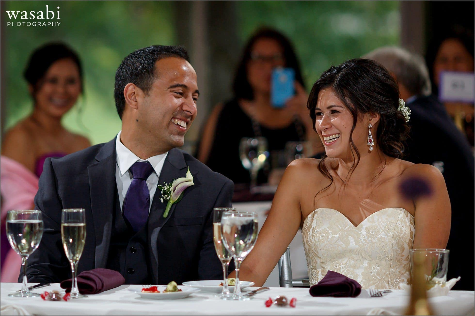 bride and groom laugh during toast at South Shore Cultural Center wedding reception photos