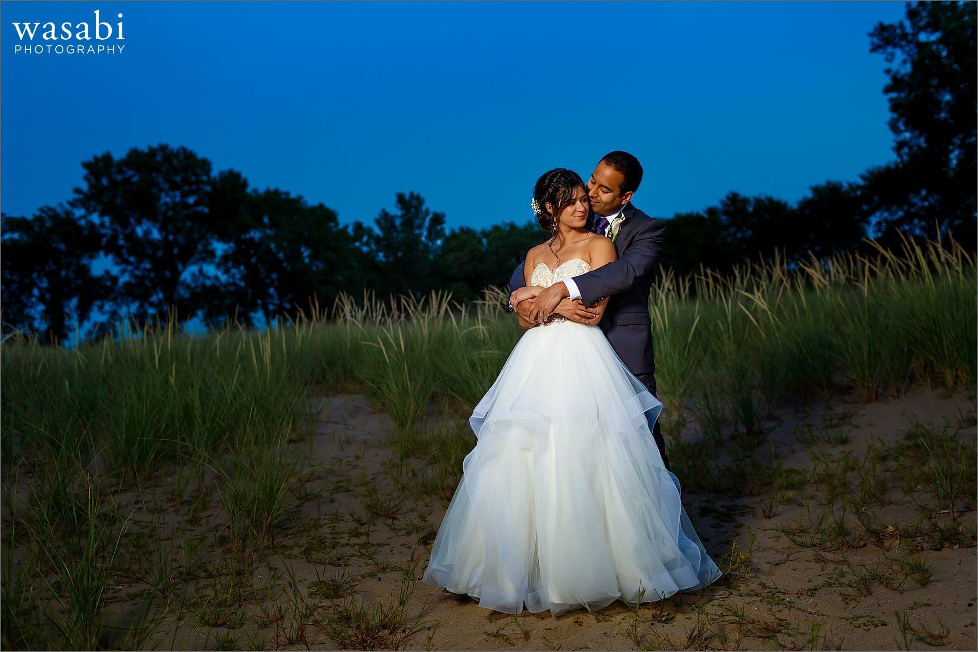 bride and groom pose for South Shore Cultural Center wedding portraits blue sky on beach