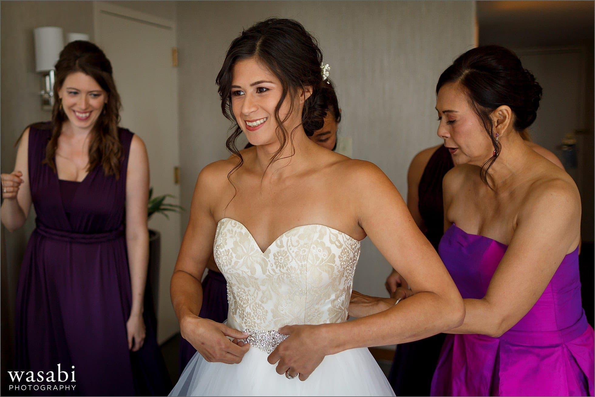 bride puts on wedding dress while getting ready for a wedding at Sheraton Grand Hotel in Chicago