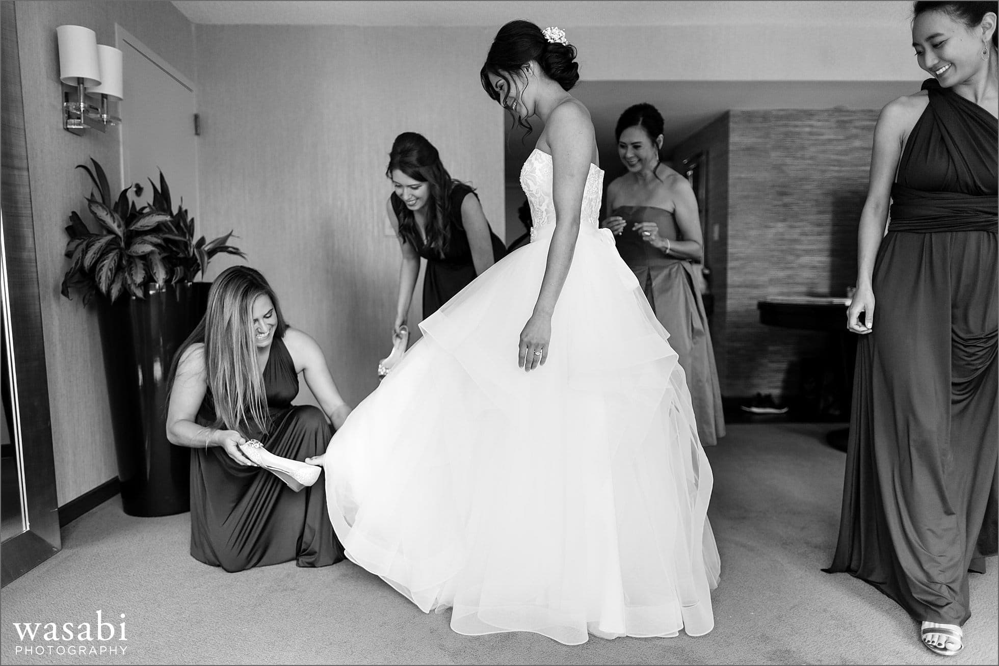 bridesmaid helps bride put on a shoe while getting ready for her wedding at Sheraton Grand Hotel in Chicago