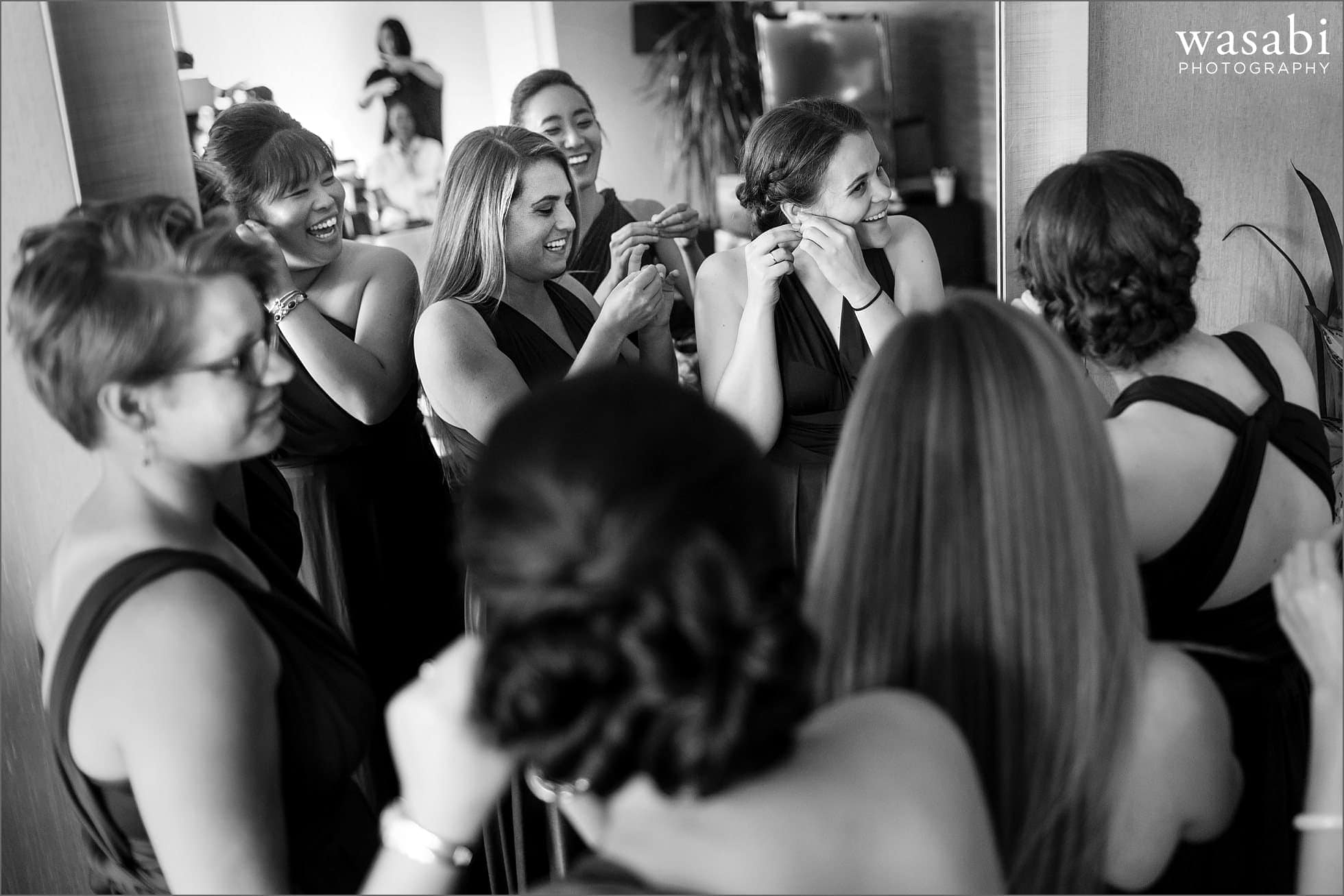 bridesmaids in a circle put on their earrings together while getting ready for a wedding at Sheraton Grand Hotel in Chicago