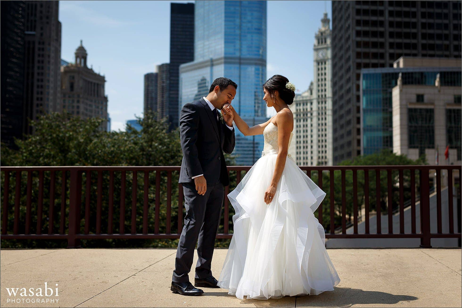 groom kisses brides hand at first look in downtown Chicago