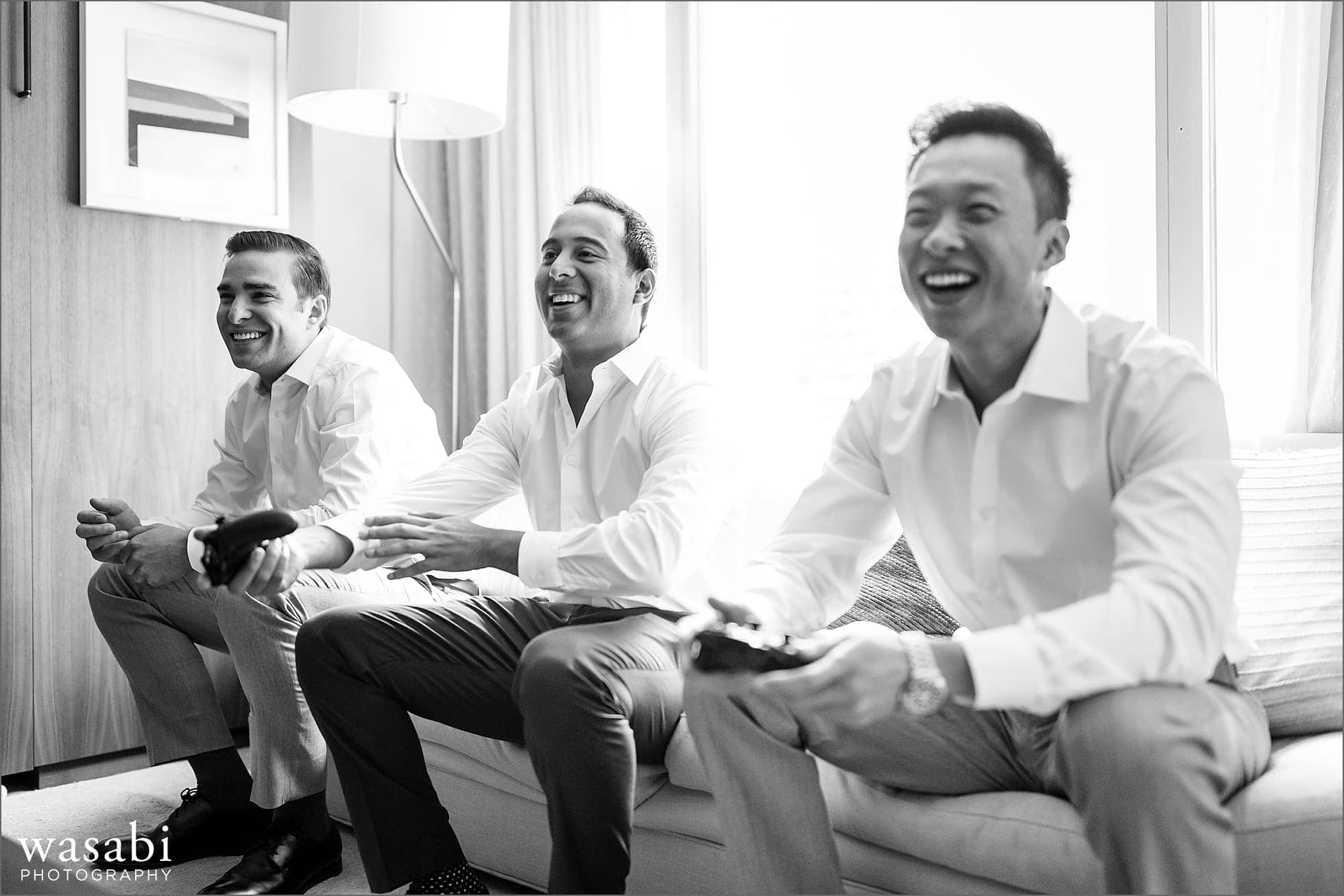 groom laughs while playing video games with groomsmen before his wedding at Sheraton Grand Hotel in Chicago