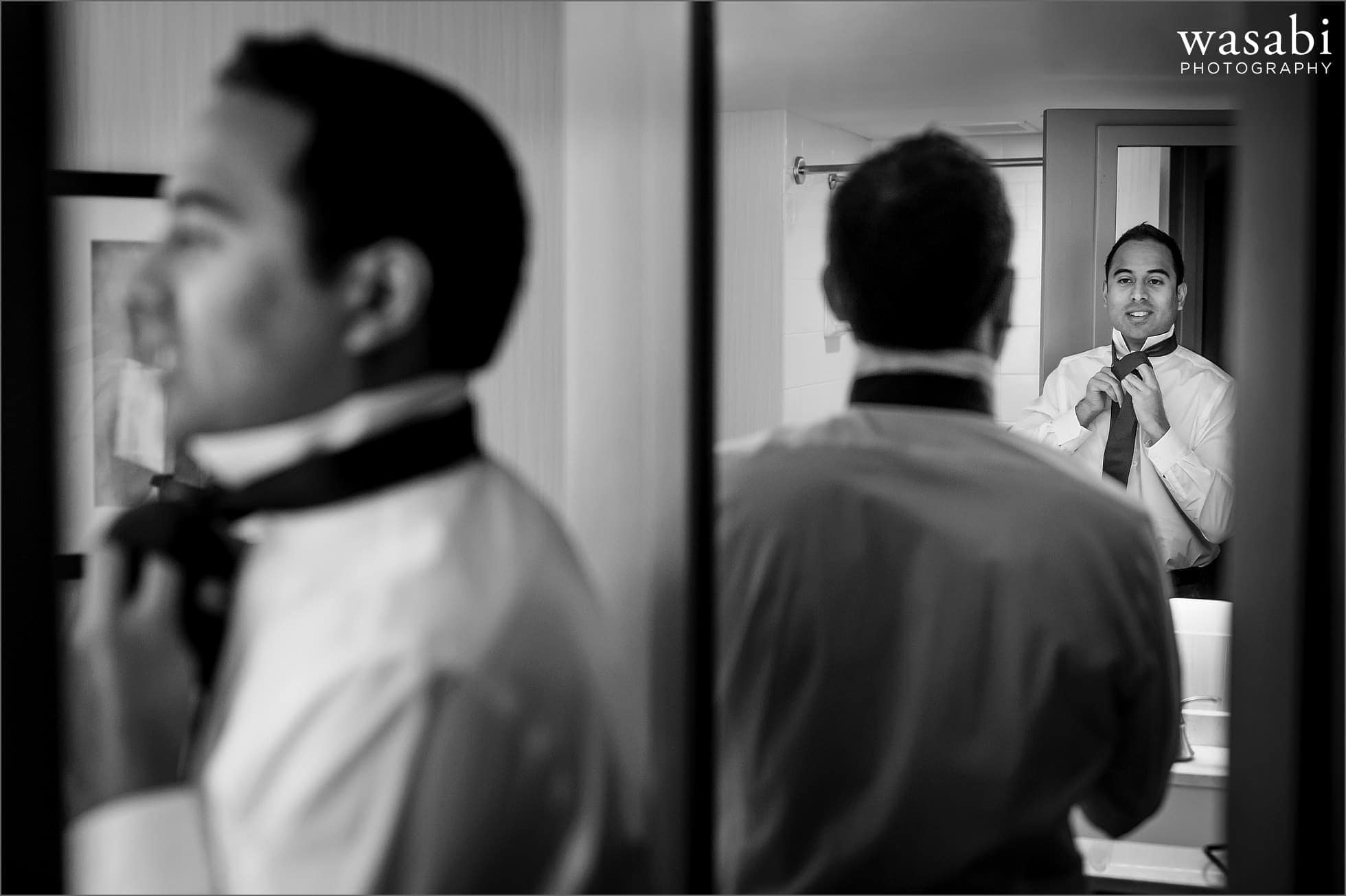 groom puts on tie in mirror while getting ready for his wedding at Sheraton Grand Hotel in Chicago