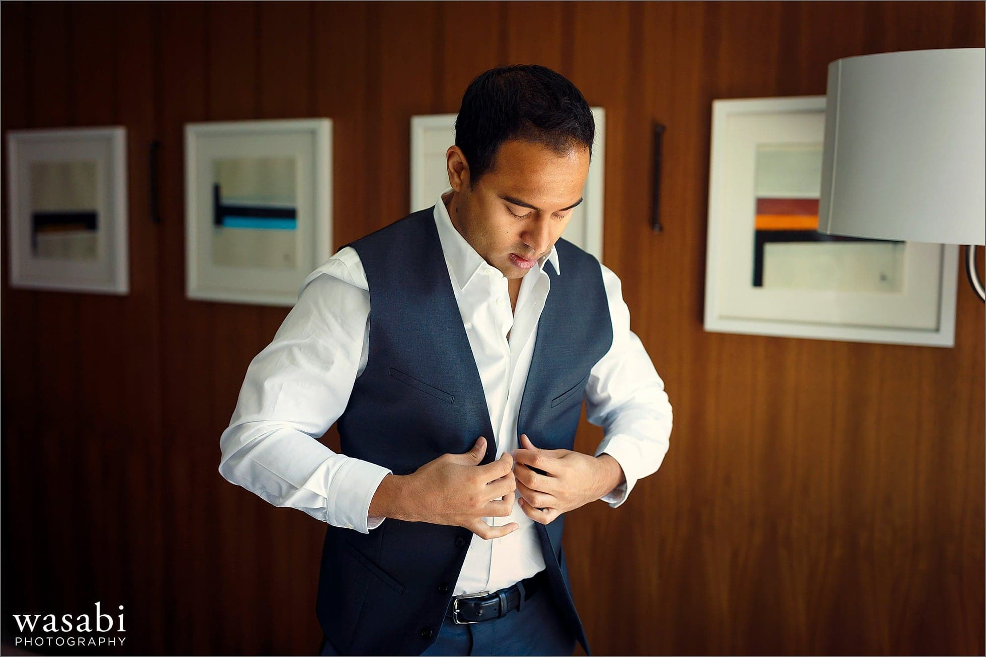 groom puts on vest while getting ready for his wedding at Sheraton Grand Hotel in Chicago
