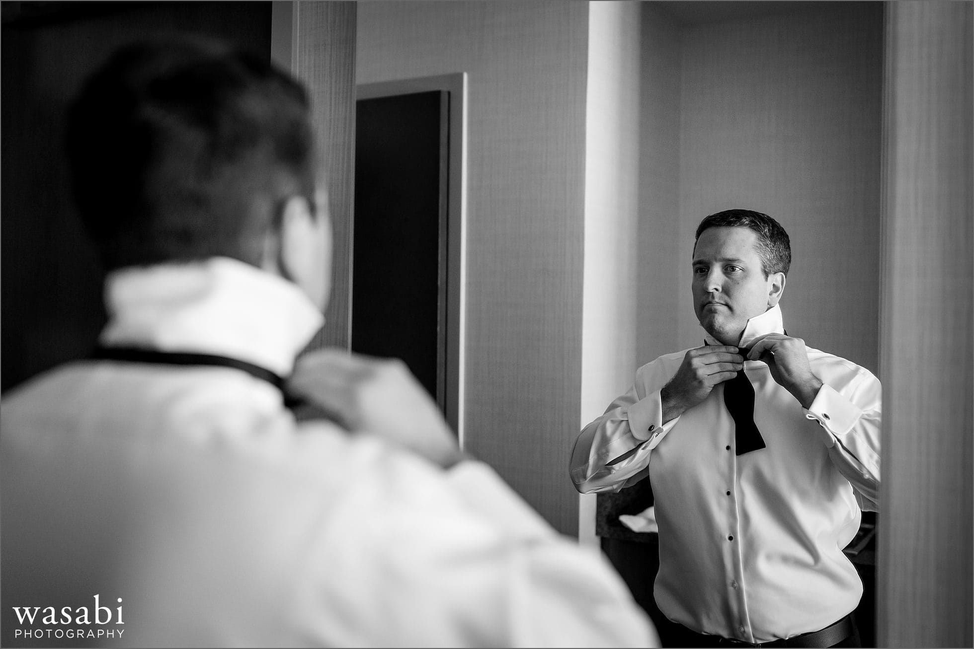black and white photo of a groom putting on a bow tie while getting ready for a wedding at Lombard Westin Hotel