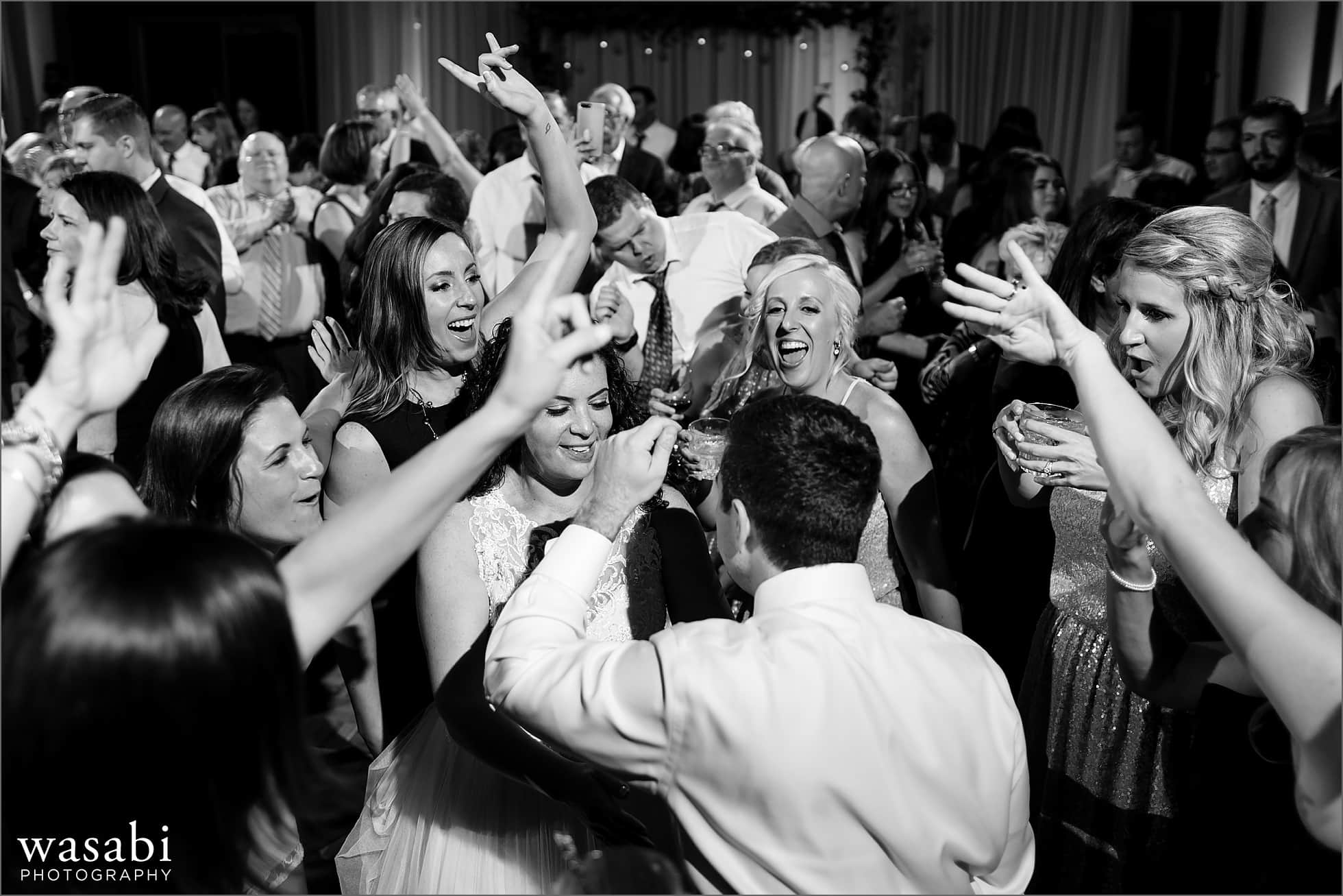 bride and groom are surrounded by friends dancing during the reception for their Lombard Westin Hotel wedding photos