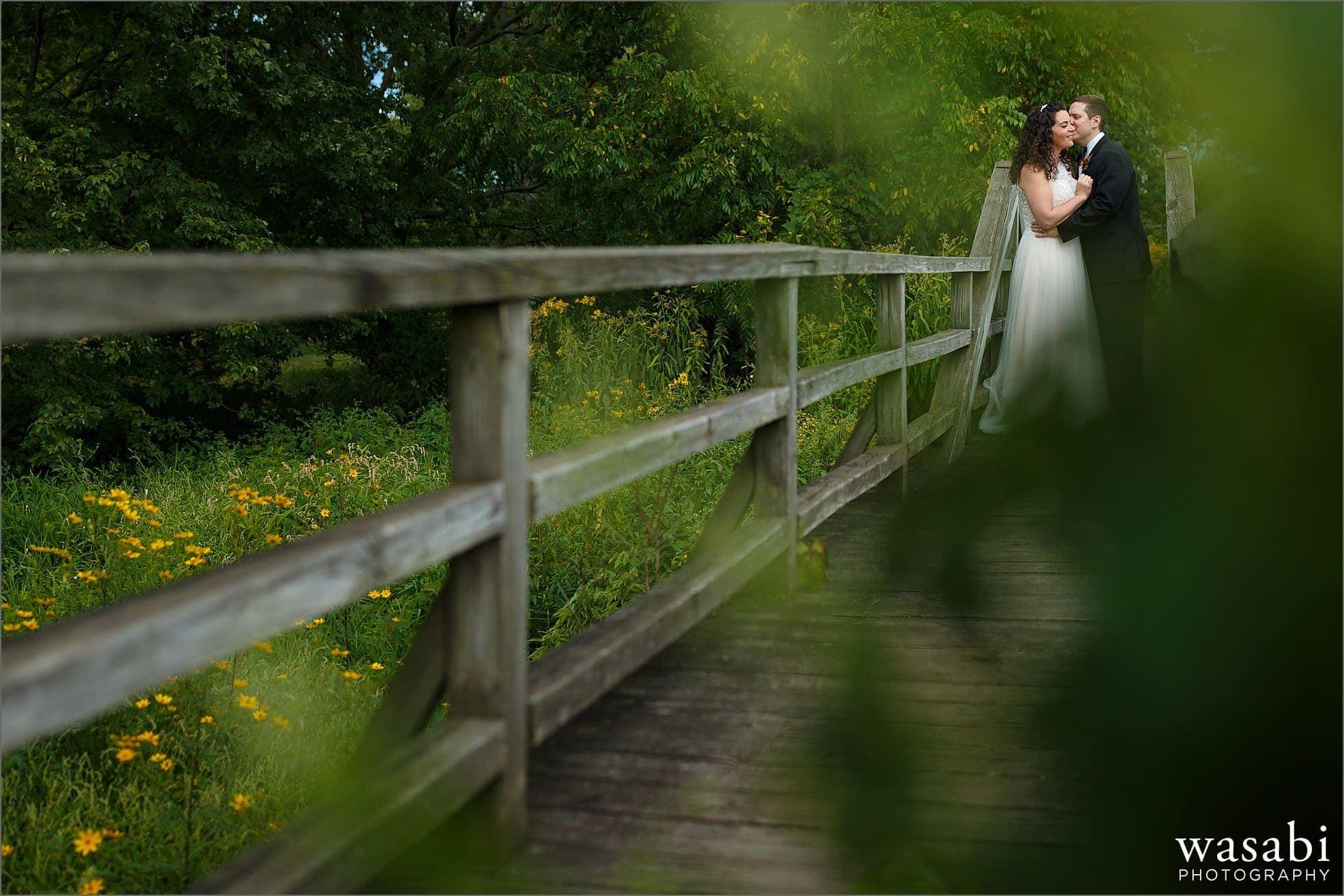 bride and groom pose for morton arboretum wedding photos on bridge