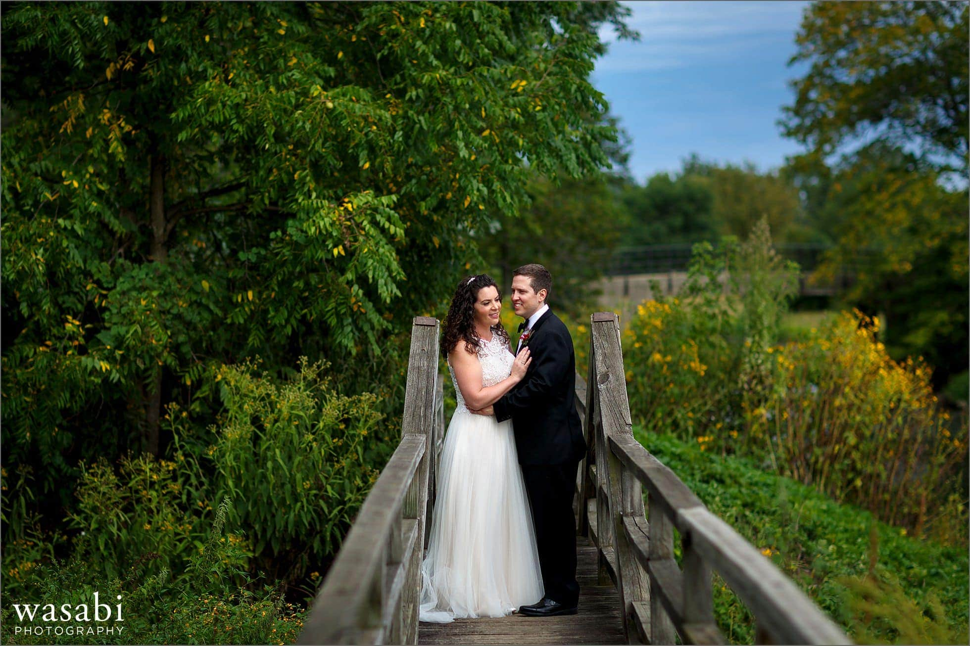 bride and groom pose for morton arboretum wedding photos on bridge