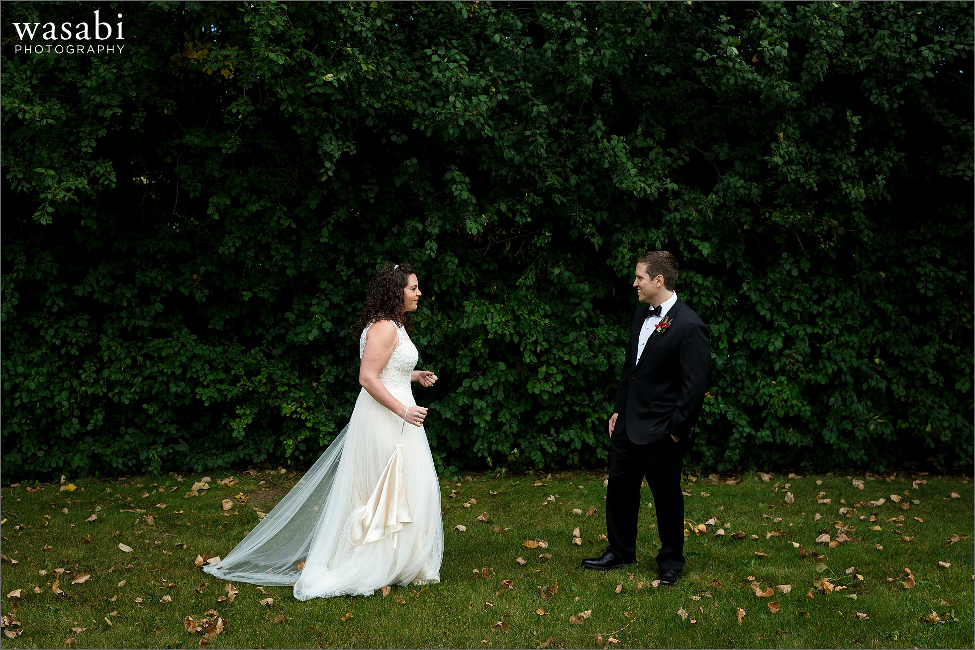 bride and groom see each other during first look in front of green trees at Lombard Westin Hotel
