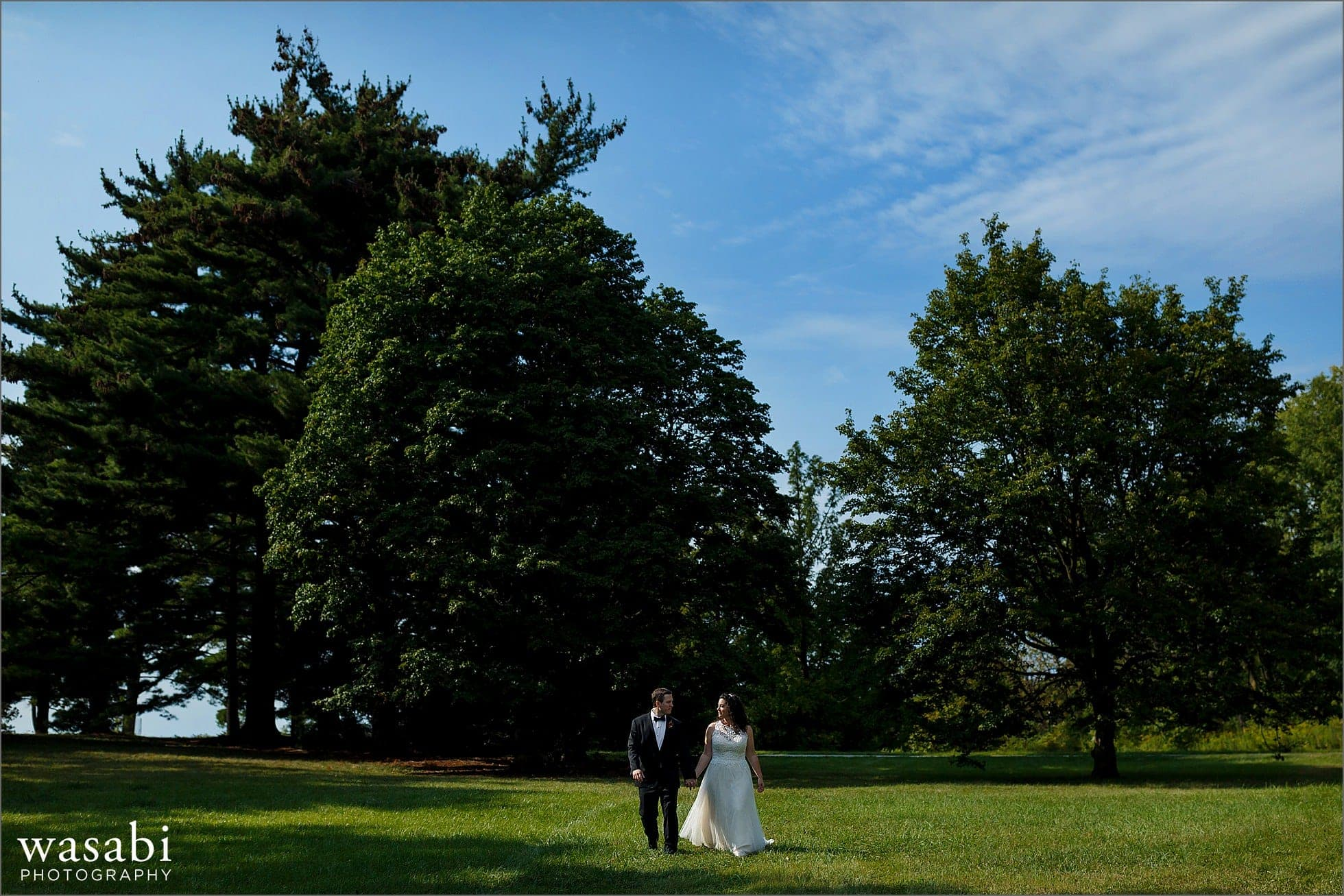 bride and groom walk during their morton arboretum wedding photos outdoors