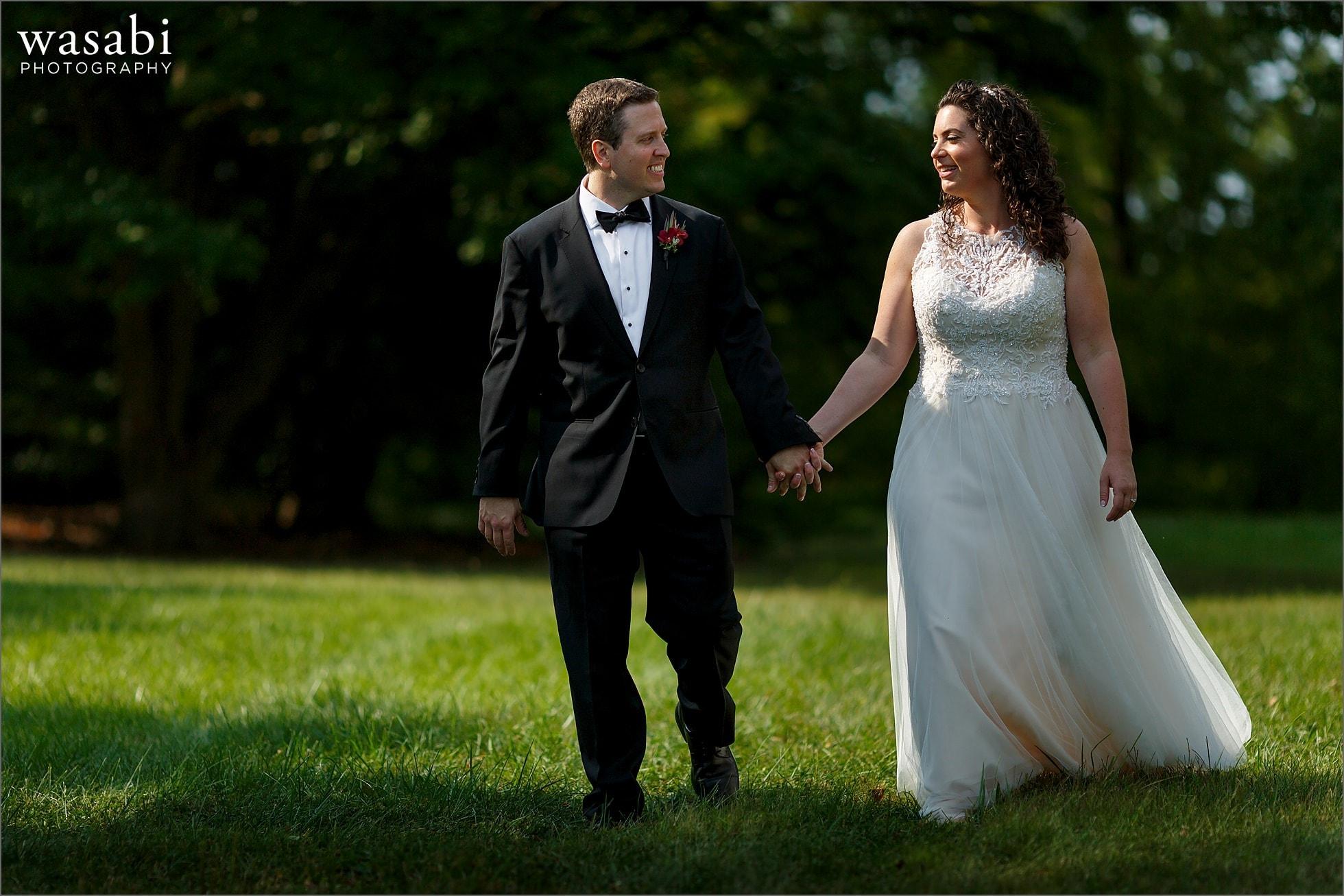 bride and groom walk during their morton arboretum wedding photos outdoors