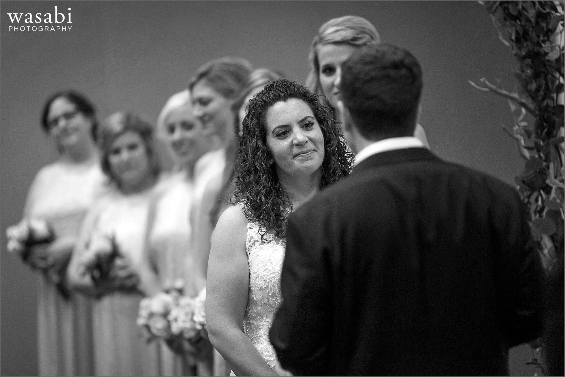 bride smiles while groom reads wedding vows during ceremony at Lombard Westin Hotel