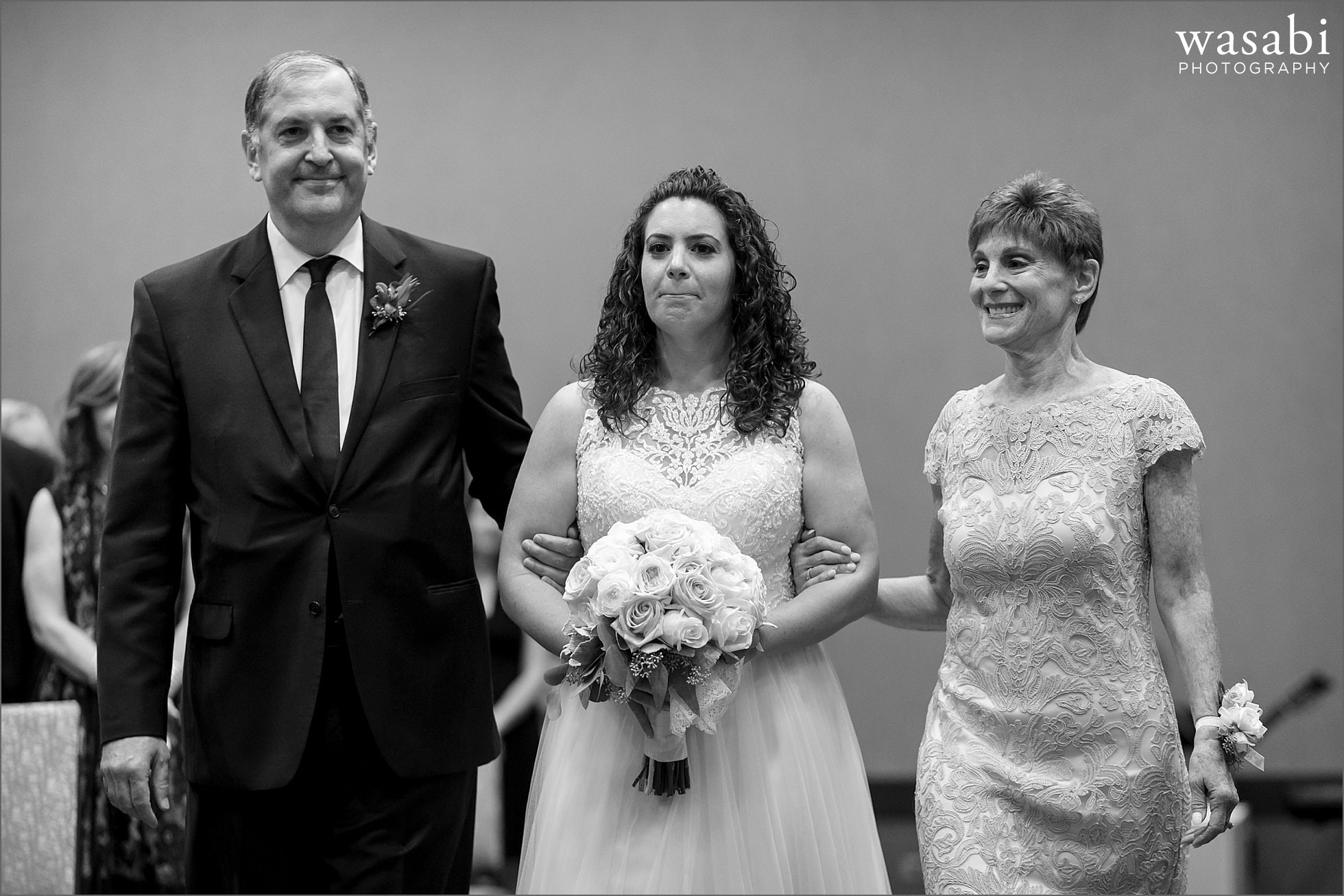 bride walks down the aisle with her parents during Lombard Westin Hotel wedding