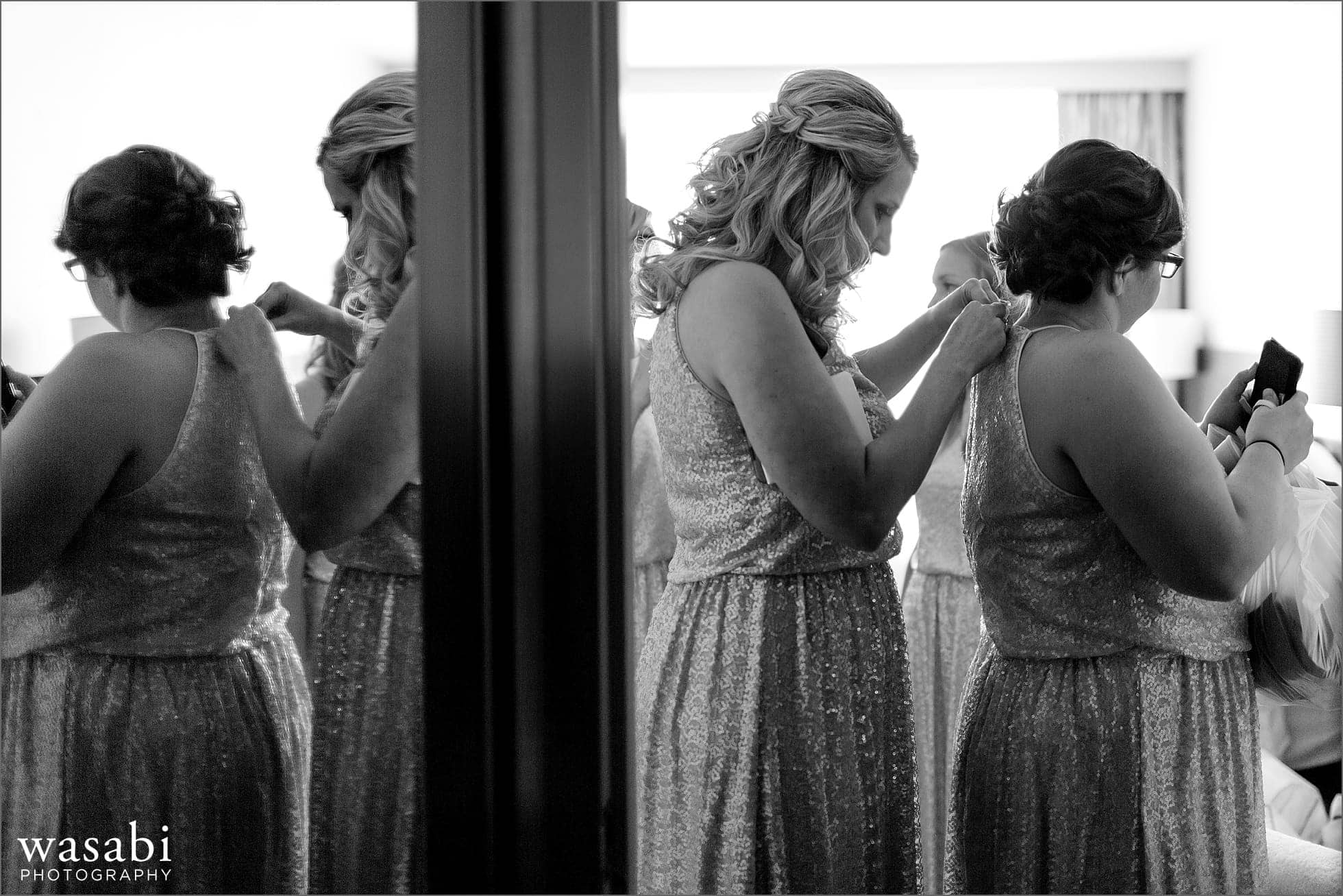bridesmaids help each other get ready putting on dresses for a wedding at Lombard Westin Hotel