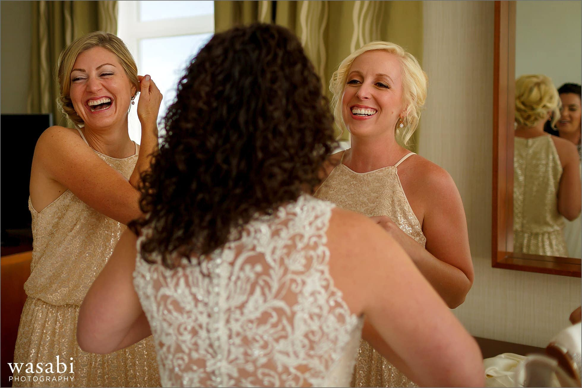 bridesmaids laugh with bride while she puts on wedding dress at Lombard Westin Hotel