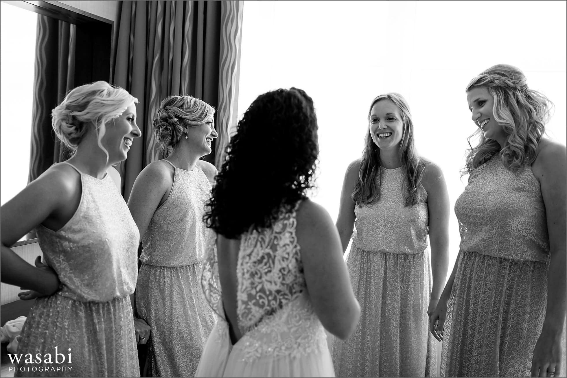bridesmaids smile at bride while she puts on wedding dress at Lombard Westin Hotel