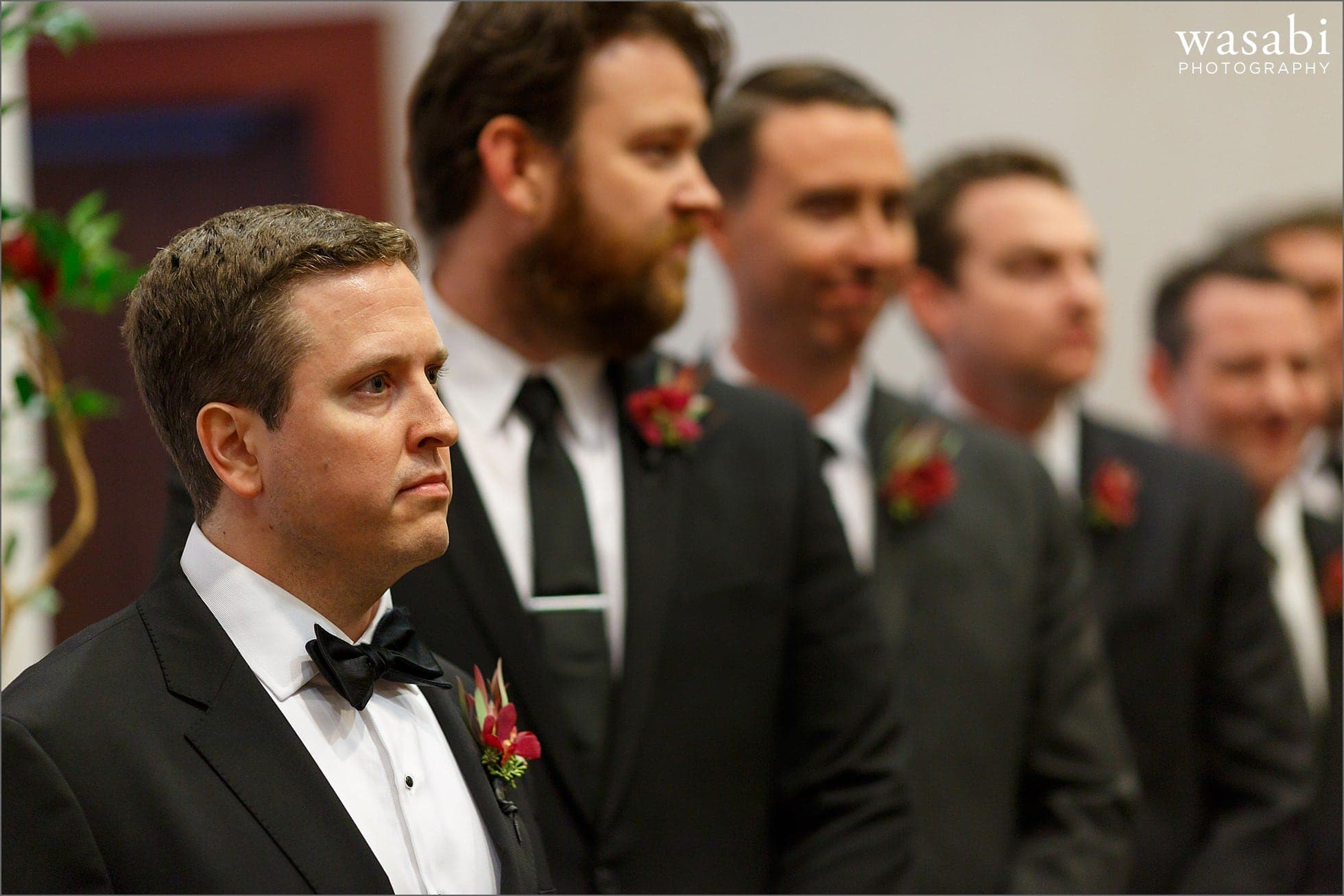groom has a serious face while watching bride walk down the aisle during Lombard Westin Hotel wedding