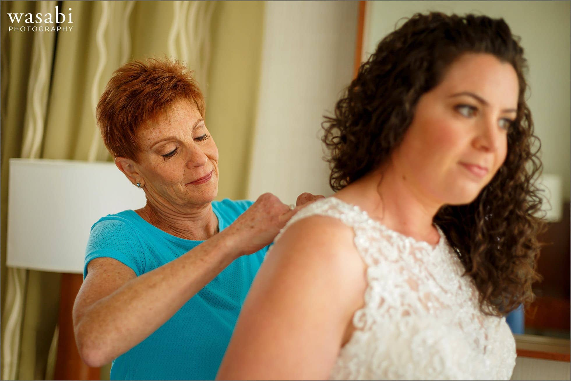 mom helps bride finish putting on wedding dress at Lombard Westin Hotel