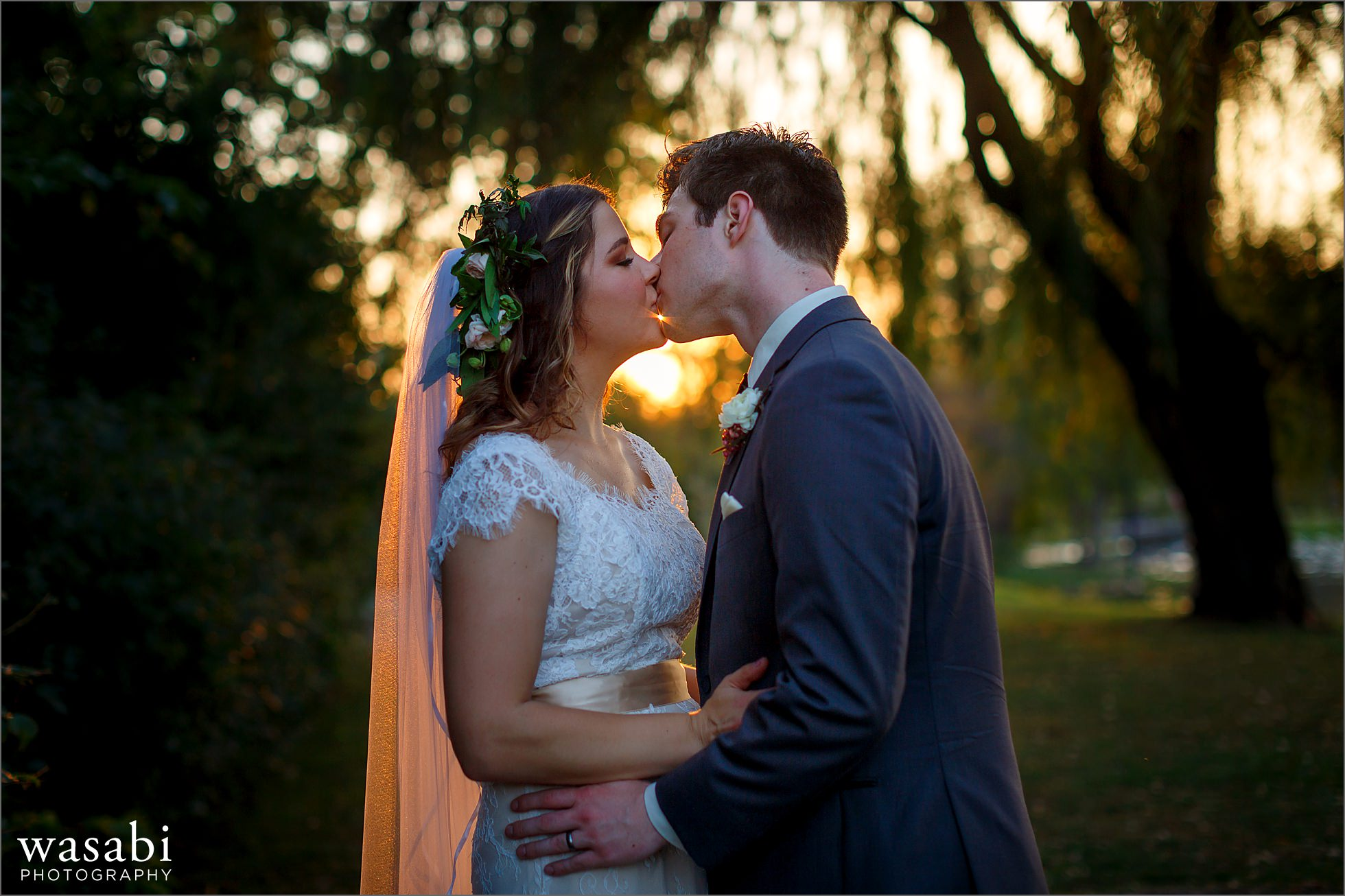 bride and groom kiss during a wedding portrait with the sunset behind them at Worth Waterfalls