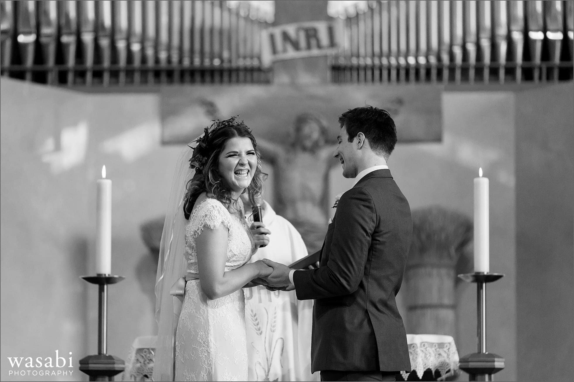bride and groom laugh during their wedding ceremony at Sacred Heart Catholic Church in Palos Hills