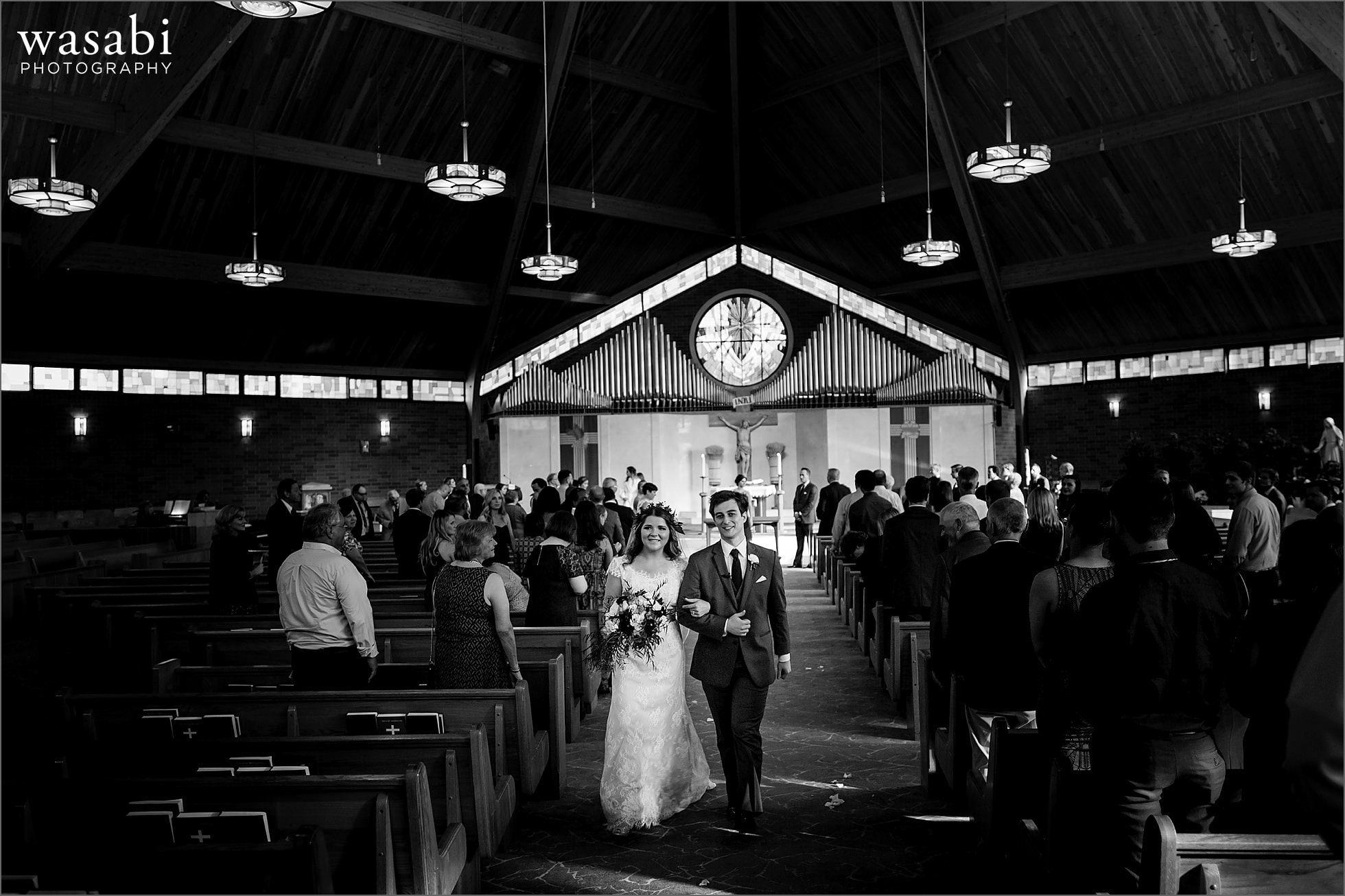 bride and groom walk back down the aisle after being married at Sacred Heart Catholic Church in Palos Hills