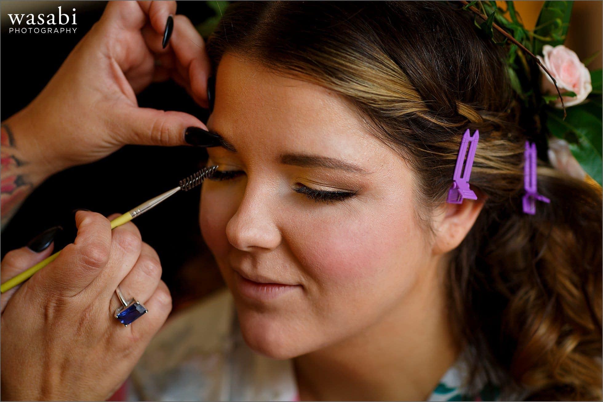 bride has her eye makeup applied while getting ready for her wedding at DoubleTree Inn in Alsip