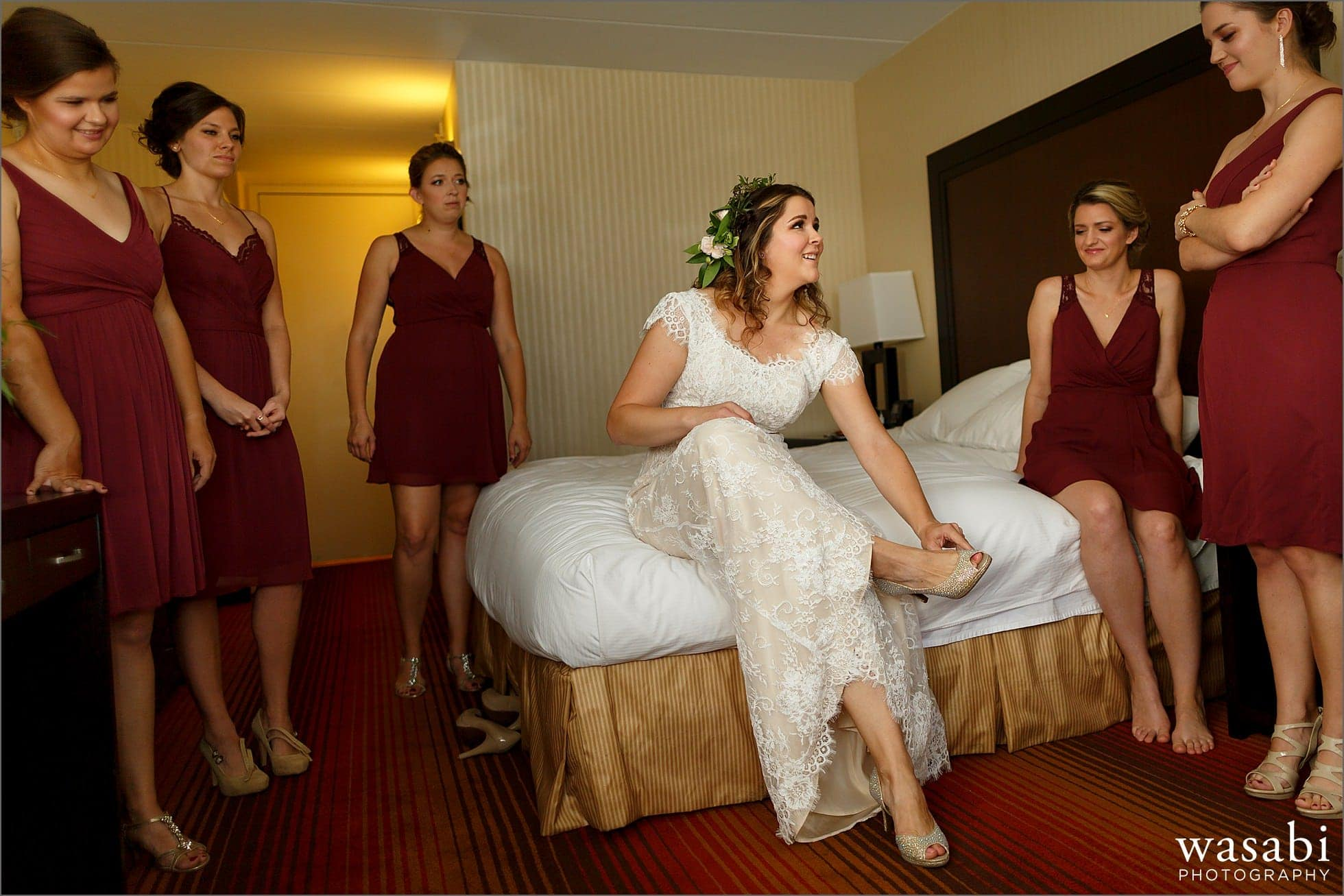 bride puts on her shoes while getting ready for her wedding at DoubleTree Inn in Alsip