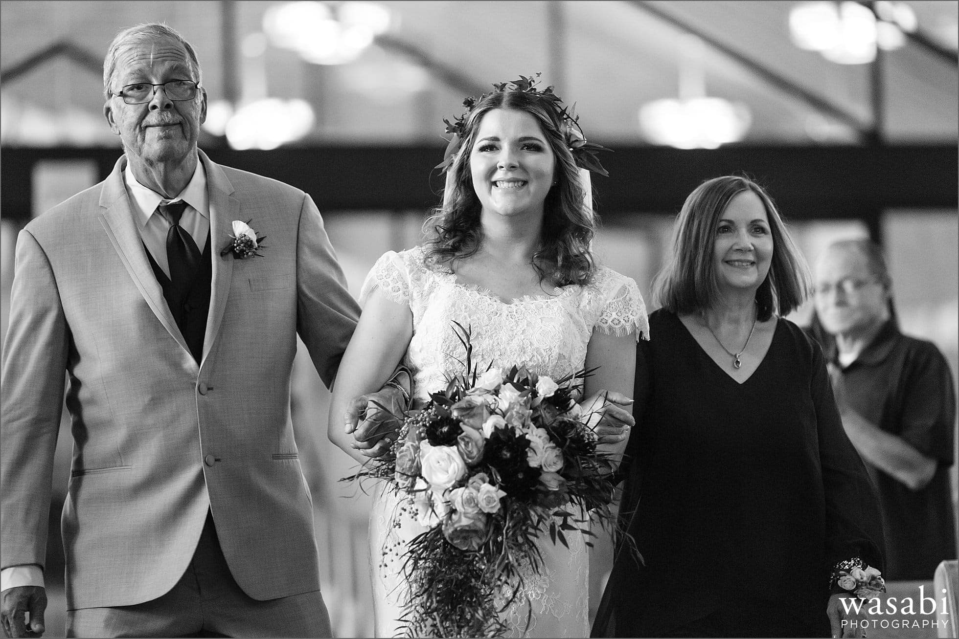 bride walks down the aisle with her parents during her wedding at Sacred Heart Catholic Church in Palos Hills