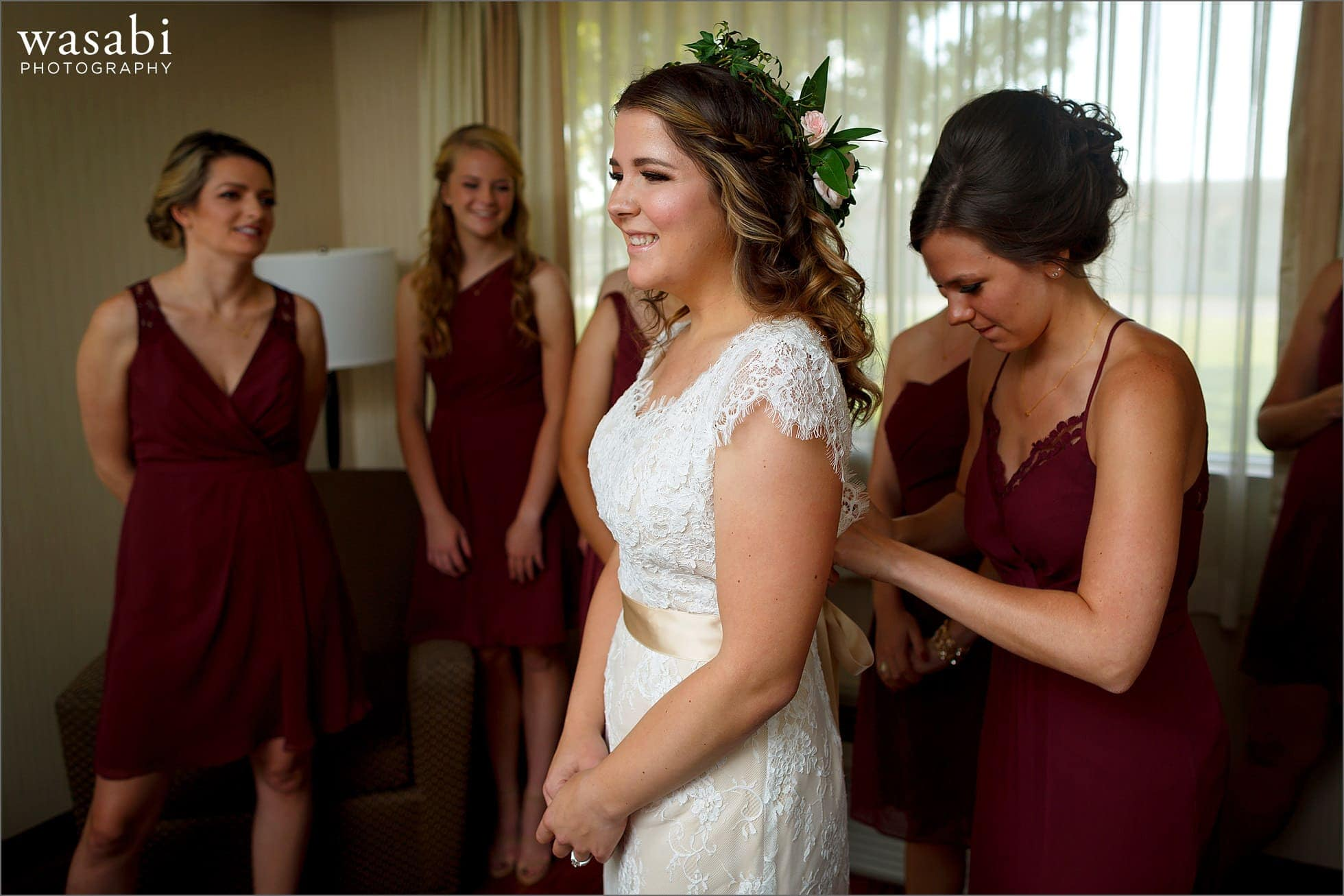 bridesmaids help bride with dress while getting ready for her wedding at DoubleTree Inn in Alsip