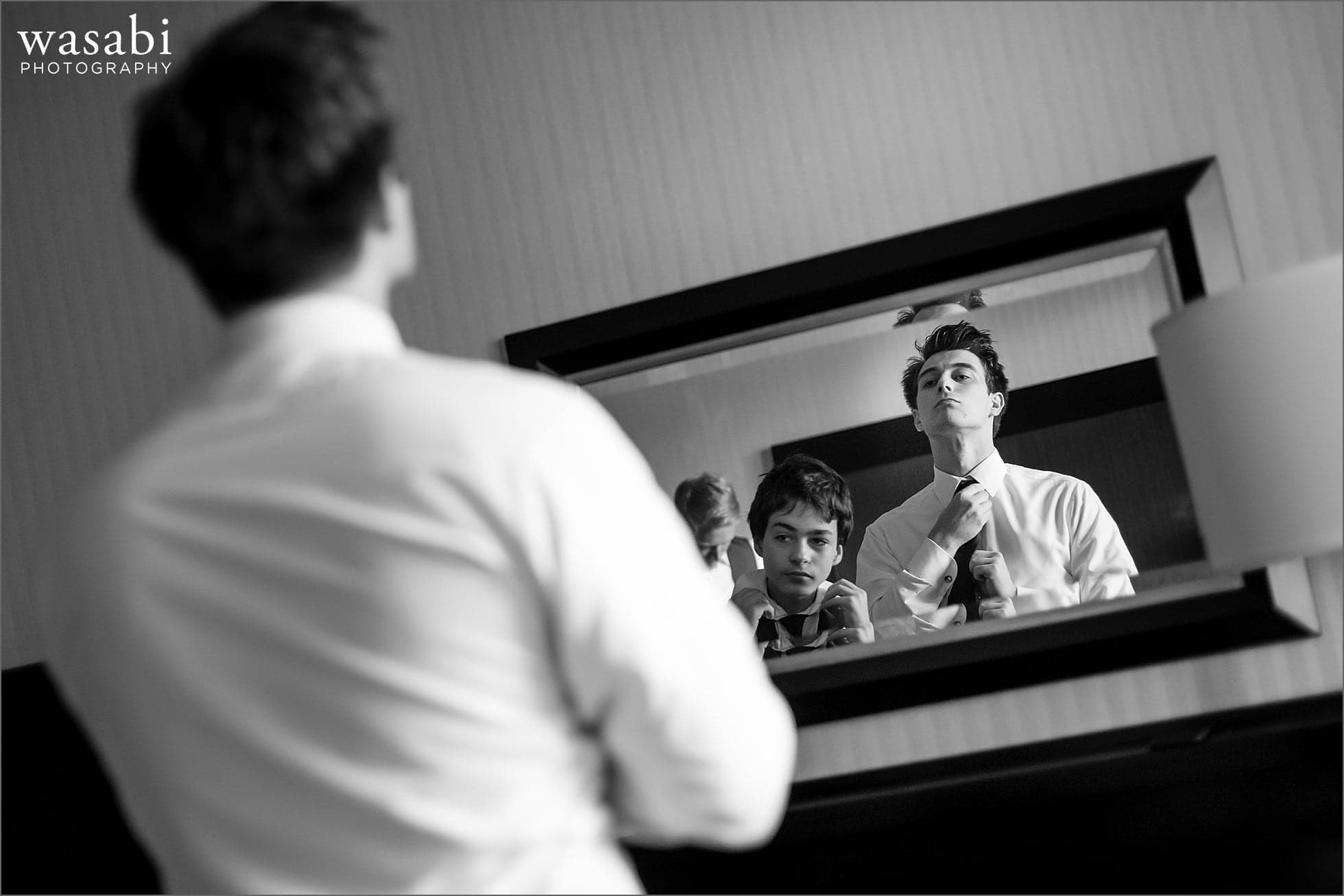 groom and brother adjust ties in the mirror at DoubleTree Inn in Alsip