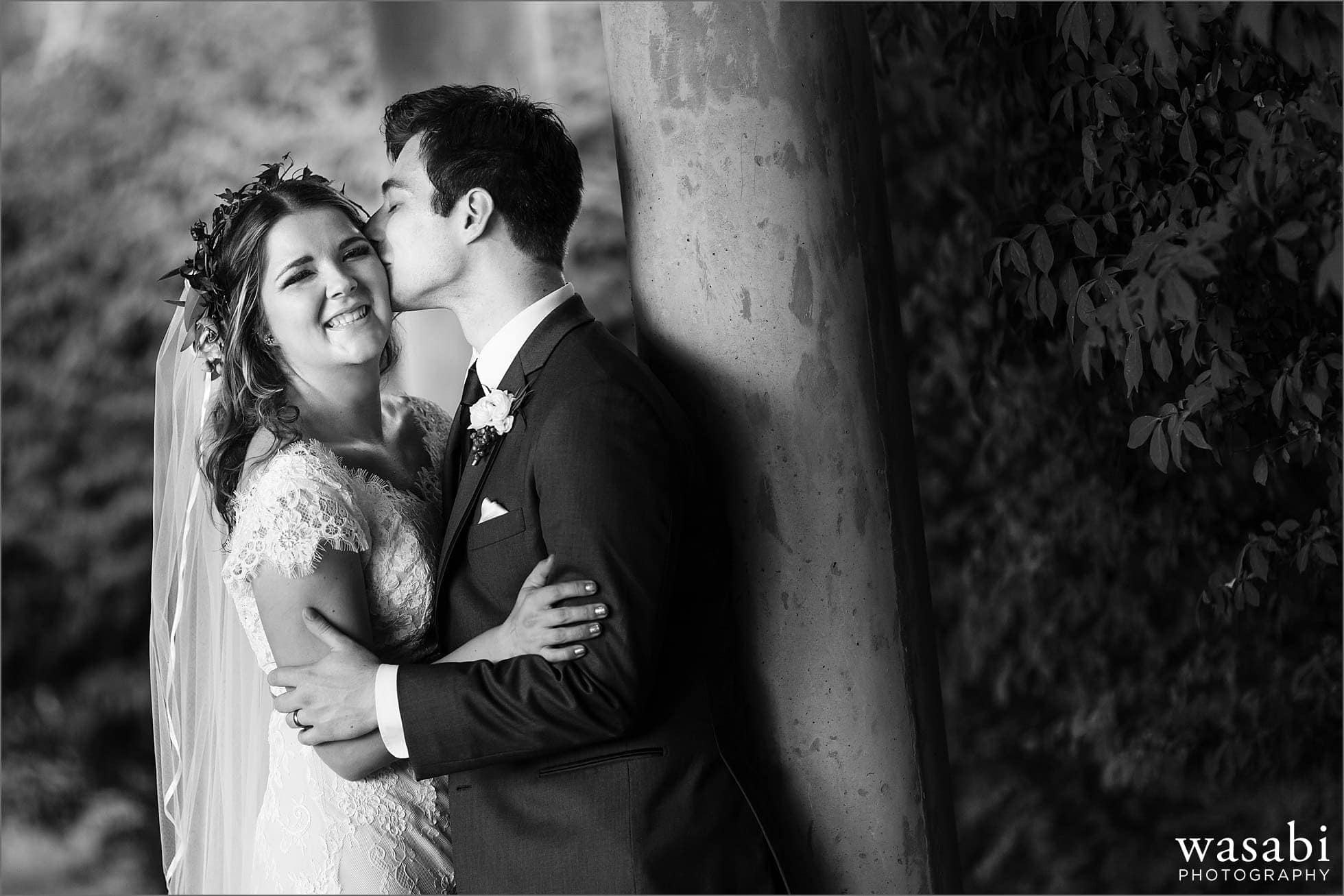 groom kisses bride on the cheek during wedding portraits at Worth Waterfalls
