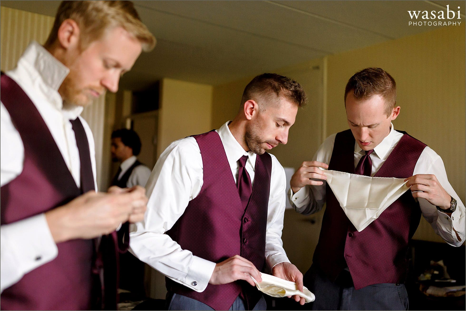 groomsmen fold pocket squares while getting ready at DoubleTree Inn in Alsip for a wedding