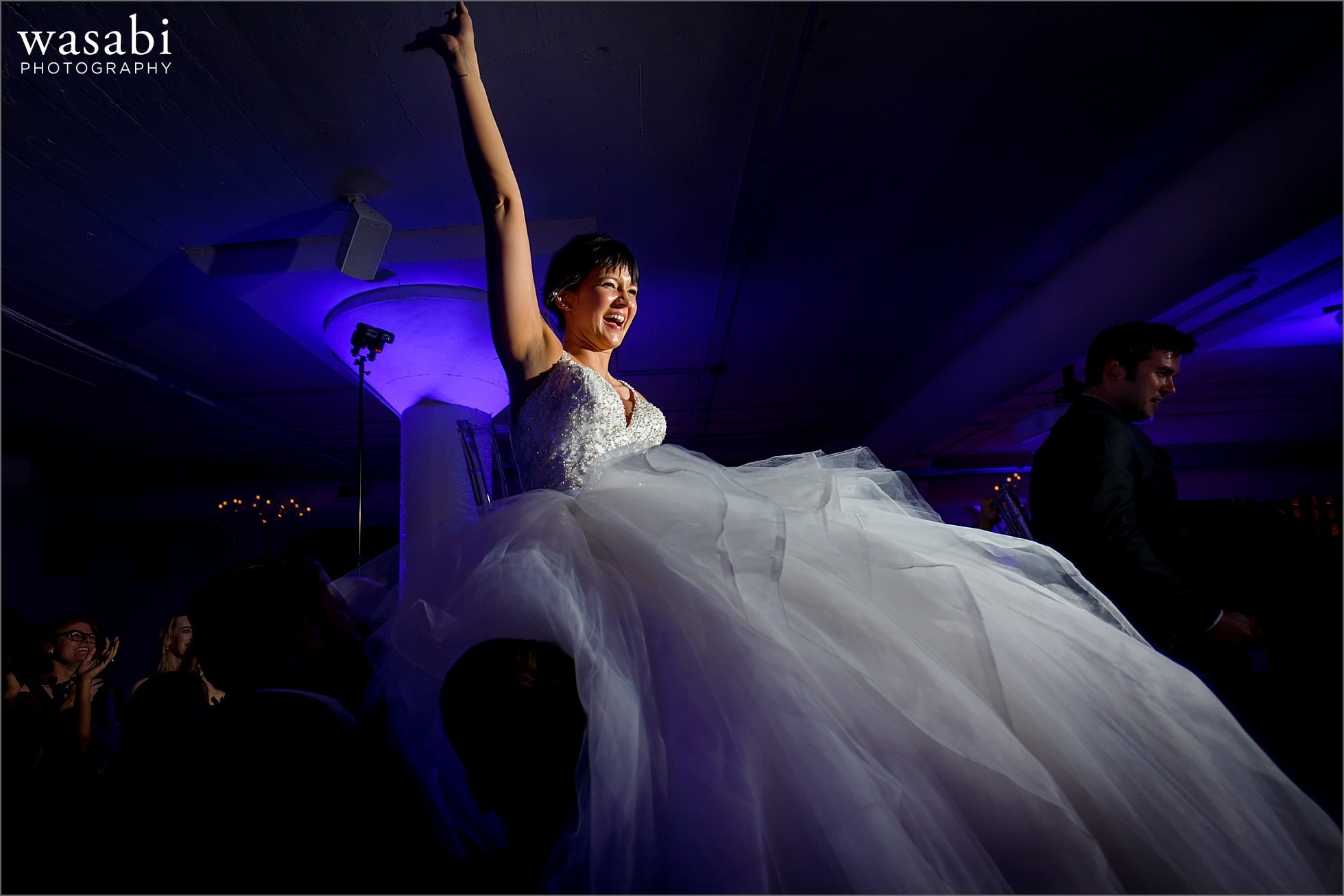 bride and groom are lifted on chairs during the Hava Nagila hora dance Room 1520 wedding reception